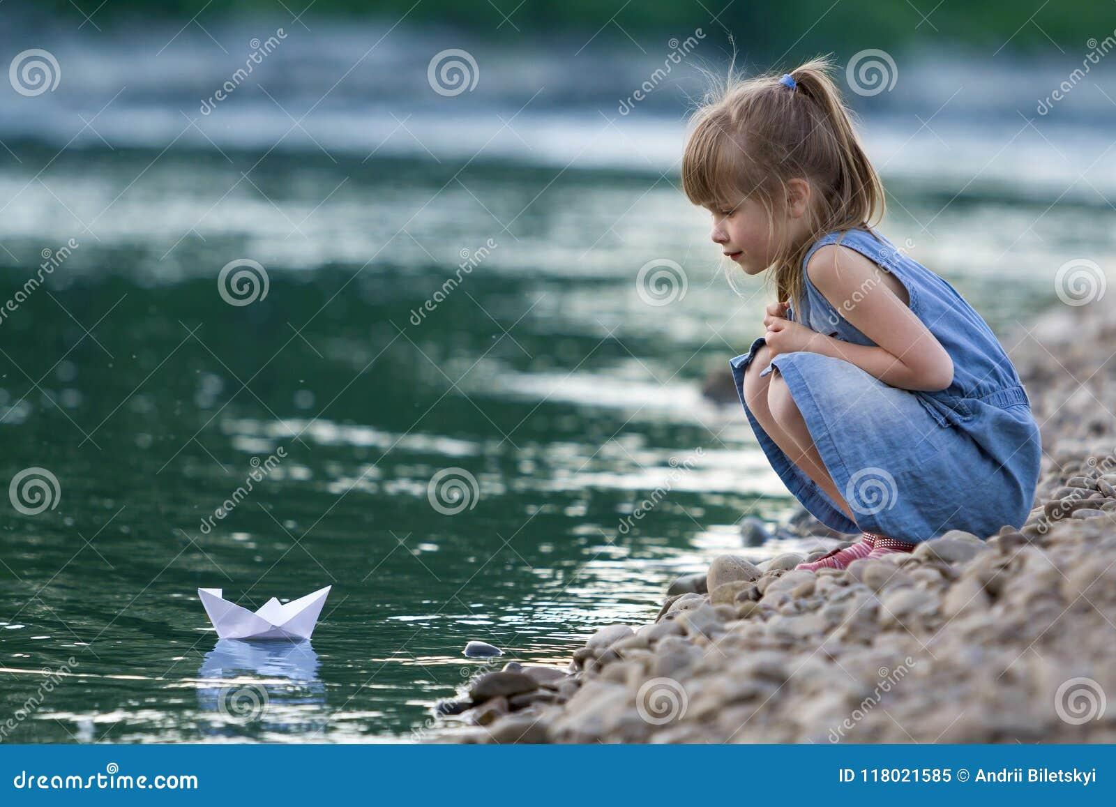 Piccola ragazza bionda sveglia adorabile in vestito blu sul pebbl di riva