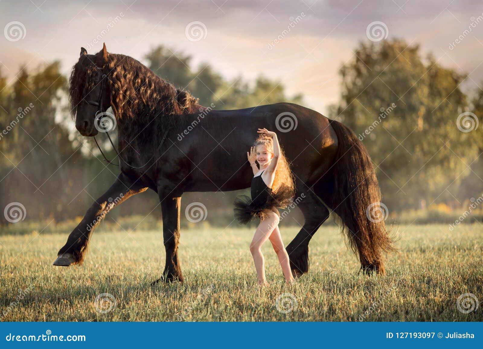 Piccola ragazza della ballerina con lo stallone frisone nero