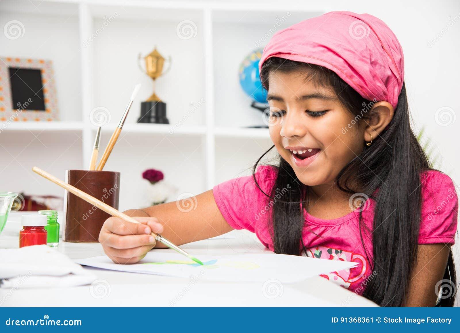 Piccola ragazza indiana occupata in disegno o pittura o coloritura