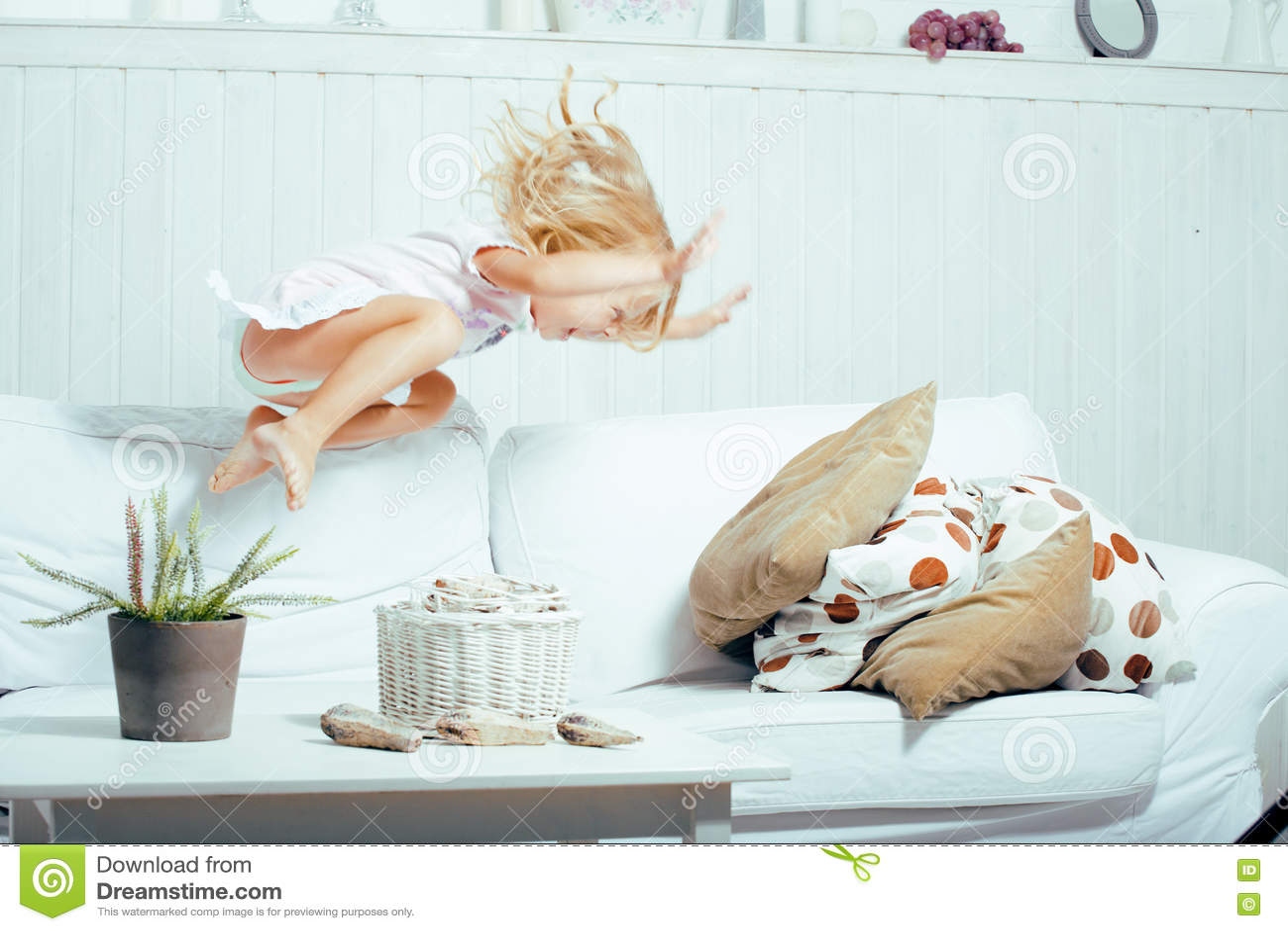 Piccola ragazza norvegese bionda sveglia che gioca sul sofà con i cuscini, solo domestico pazzo, concetto della gente di stile di
