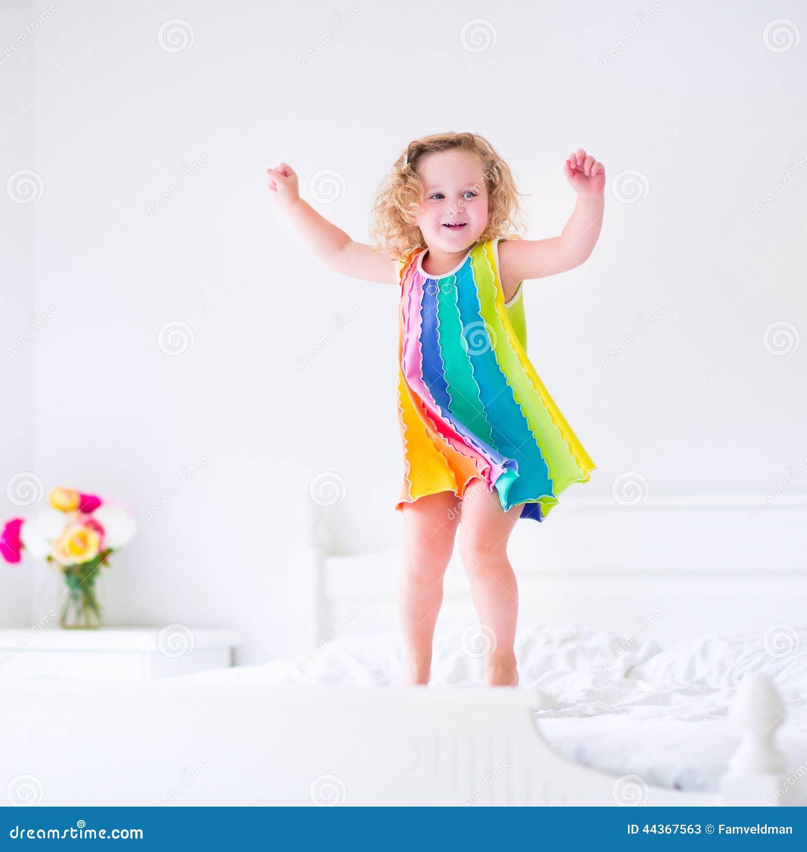 Piccola ragazza riccia sveglia del bambino che salta sul letto bianco