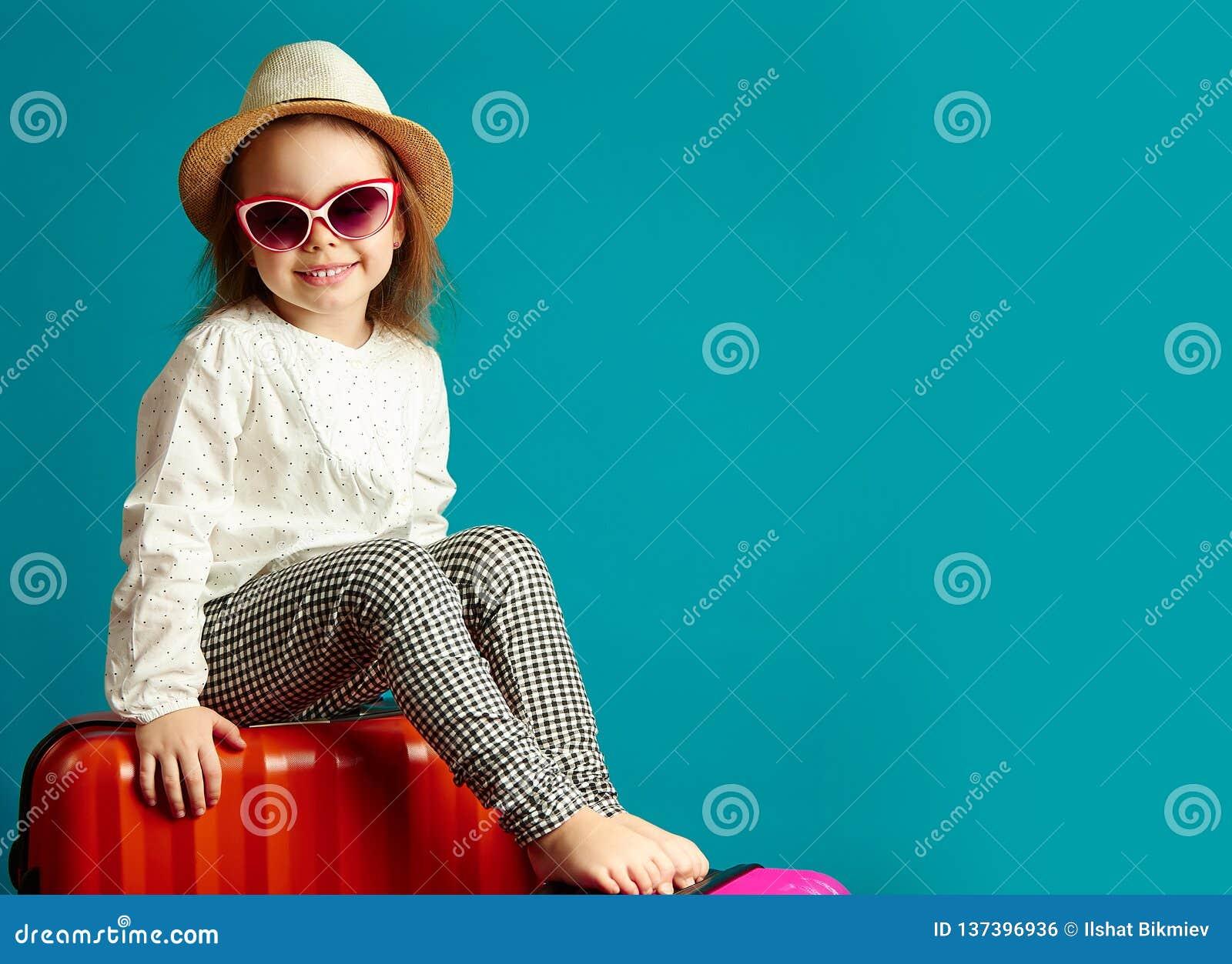 Piccola ragazza sorridente in cappello di paglia ed occhiali da sole che si siedono sulle valigie, ritratto di andare in viaggio