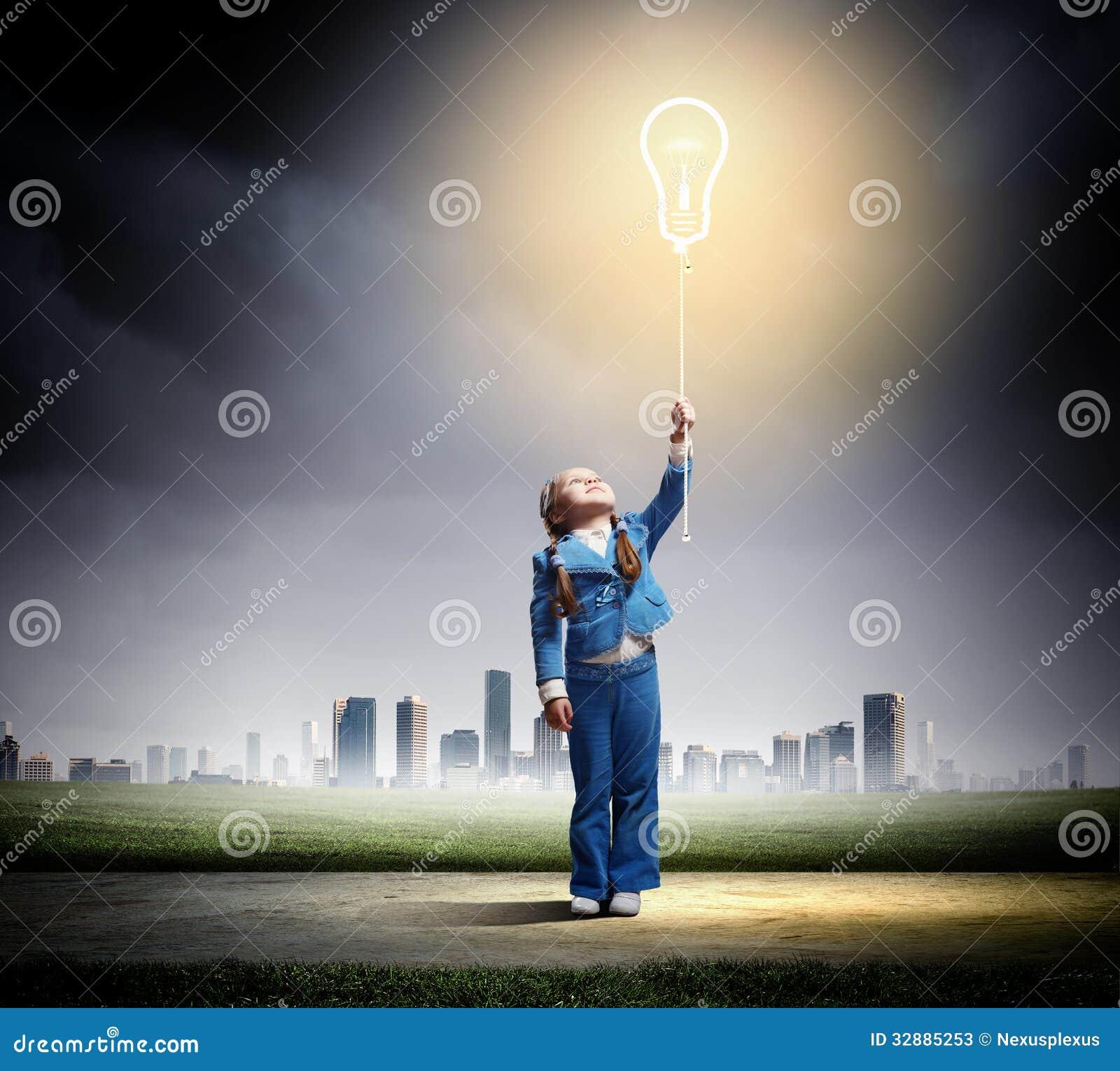 Piccola ragazza sveglia con il pallone della lampadina