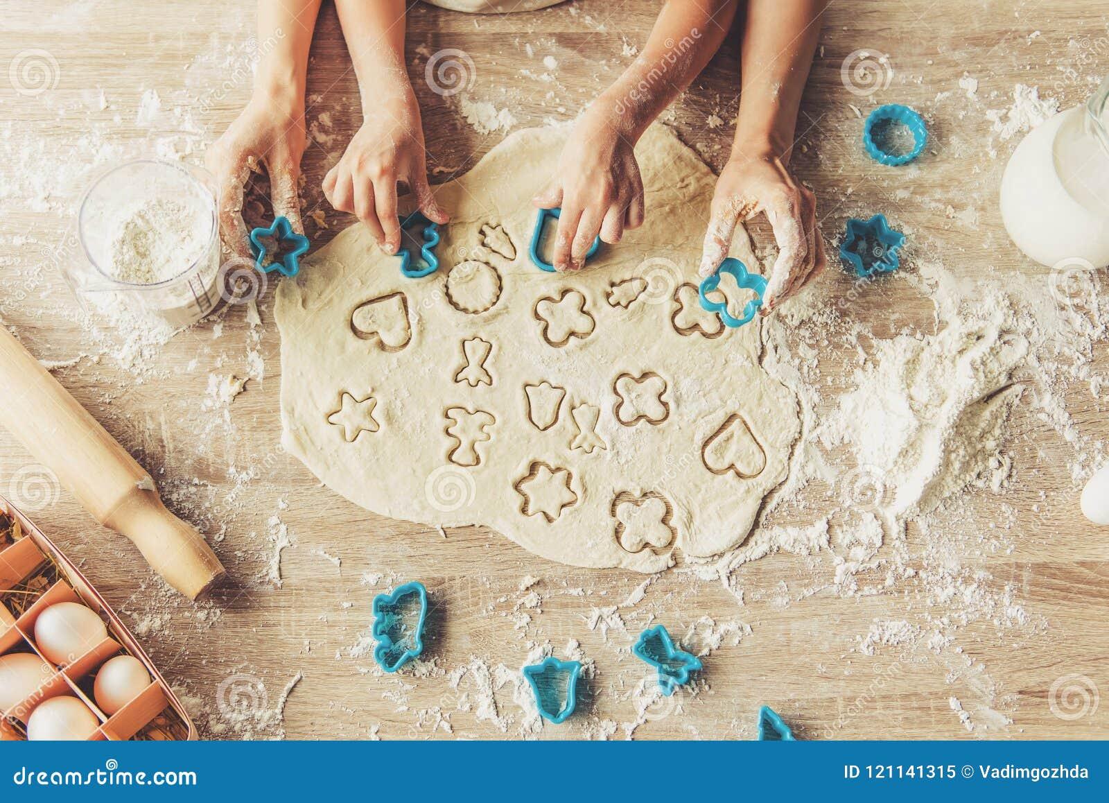 Piccola ragazza sveglia e sua la madre che preparano i biscotti