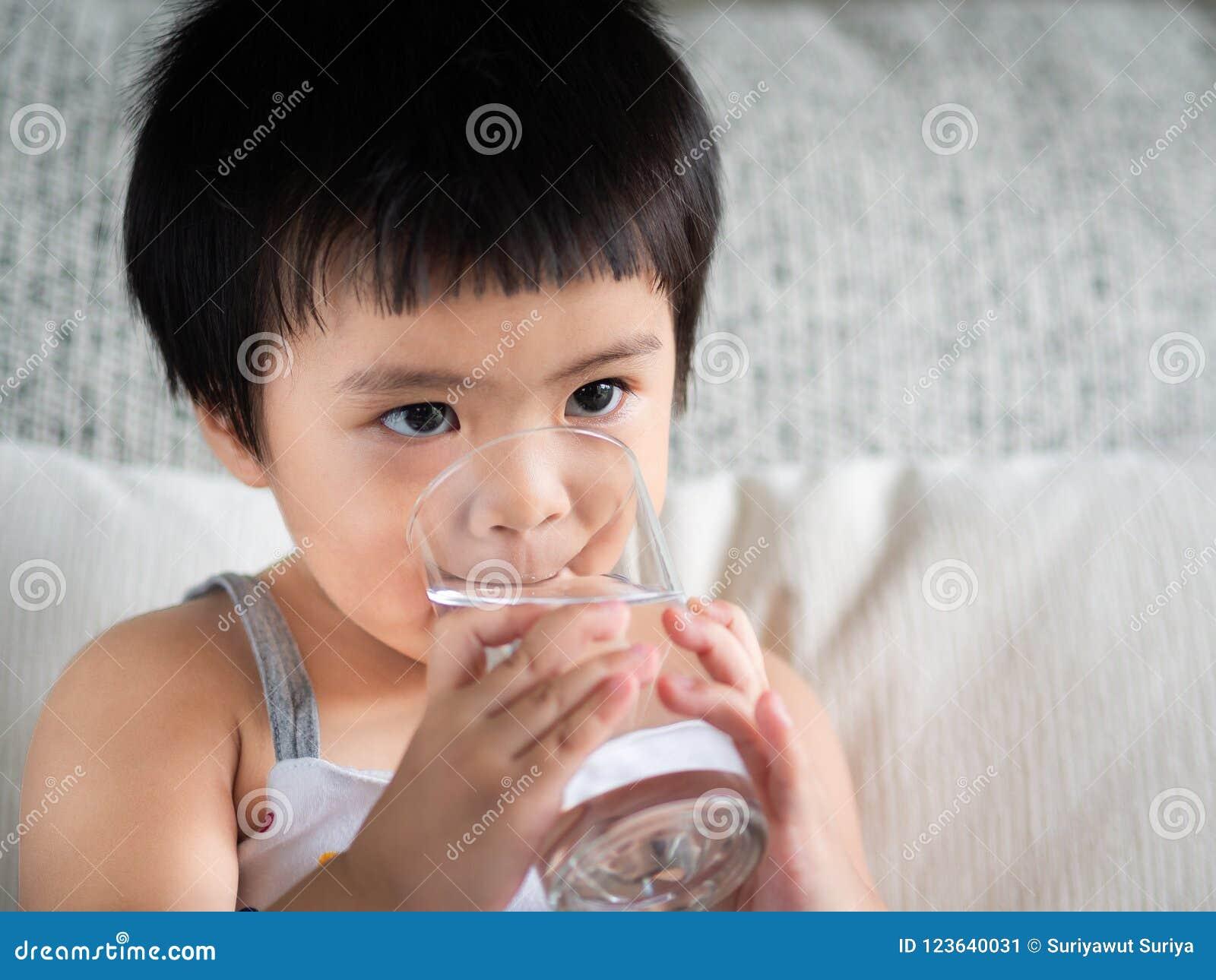 Piccola ragazza sveglia felice che tiene un vetro e che beve l acqua C