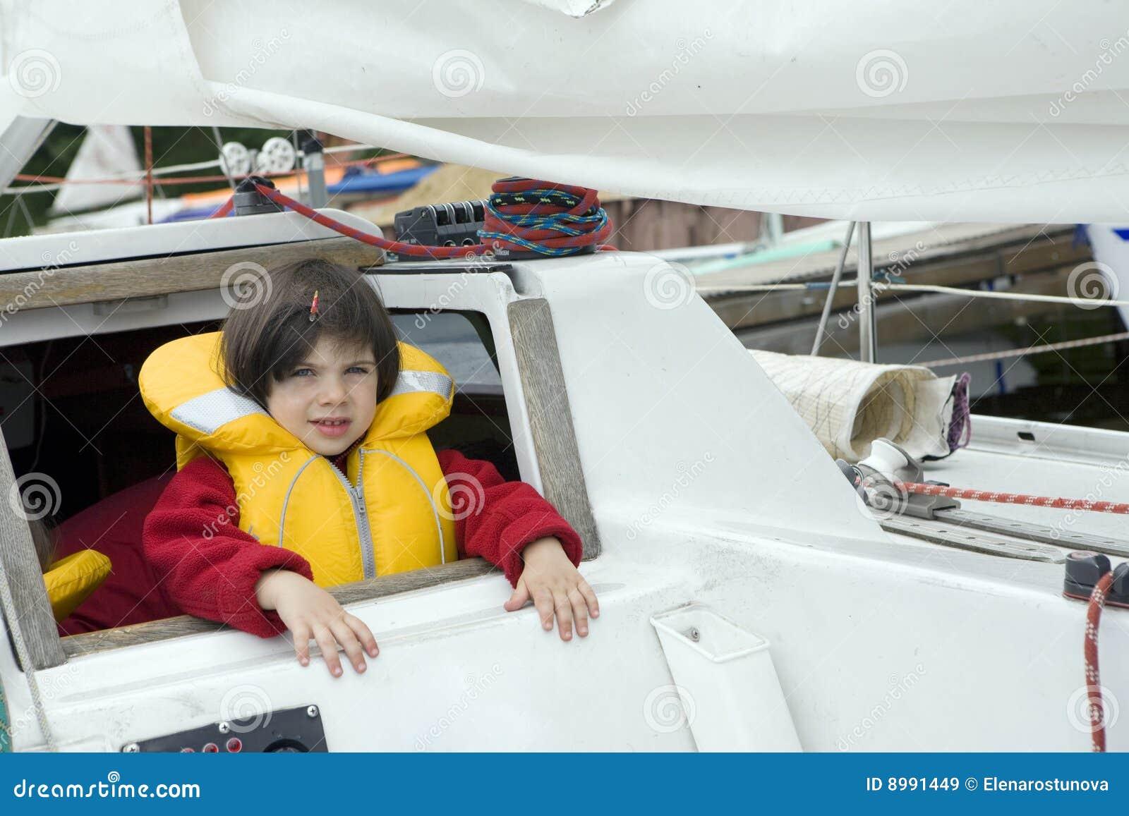 Piccola ragazza sveglia in giubbotto di salvataggio sull yacht
