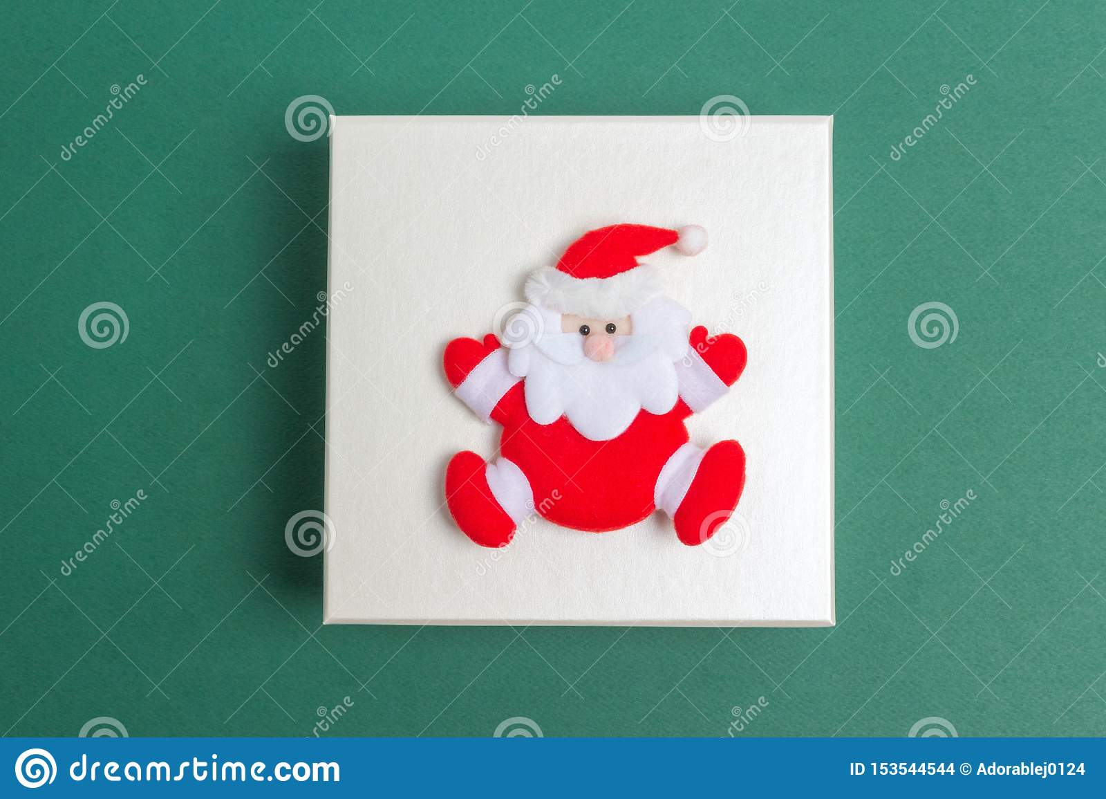 Piccola Santa Claus su un contenitore di regalo di giorno di Natale