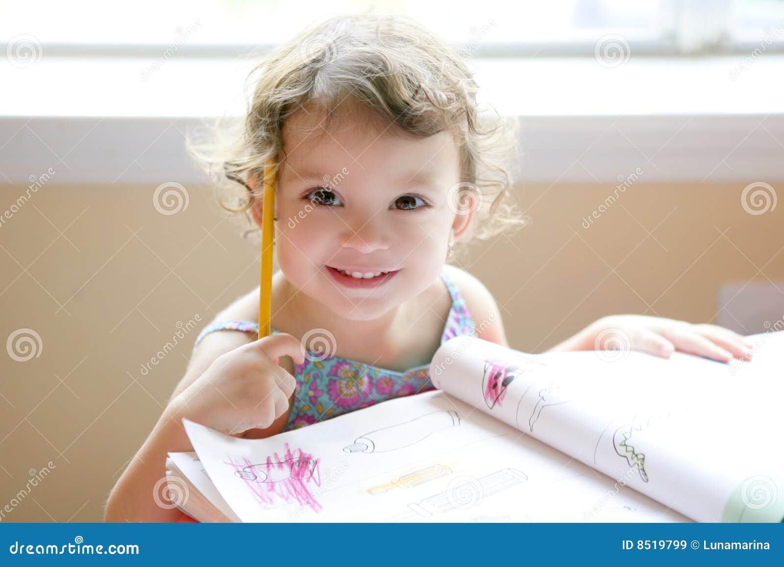 Piccola scrittura della ragazza del bambino allo scrittorio del banco