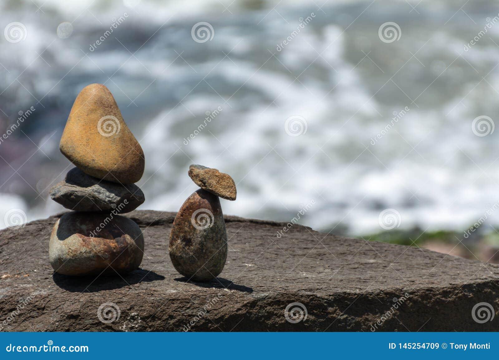 Piccola scultura due persone di somiglianza delle pietre davanti al mare, su una regione rocciosa, in Florianopolis, il Brasile