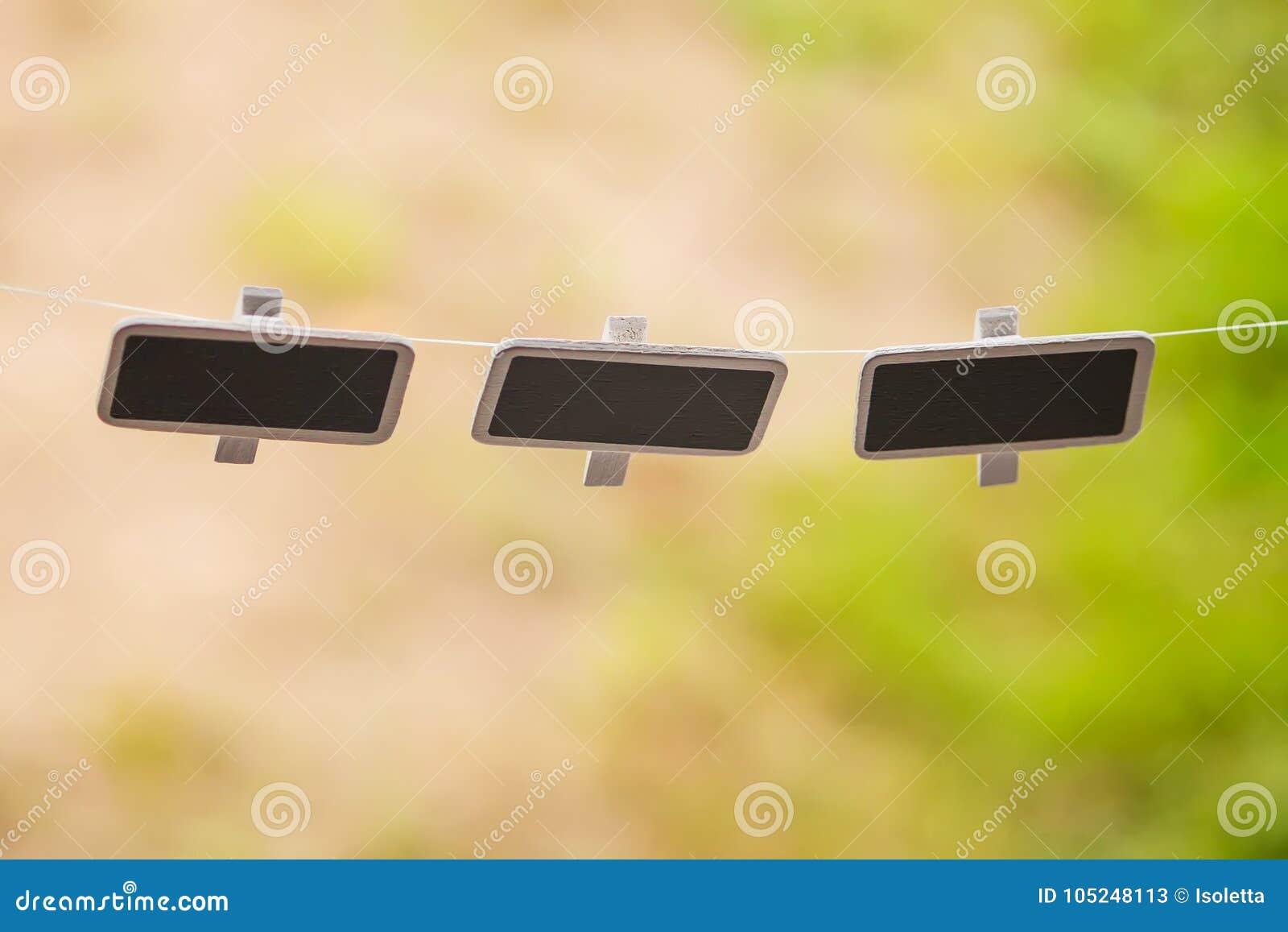 Piccole lavagne nere che appendono all aperto
