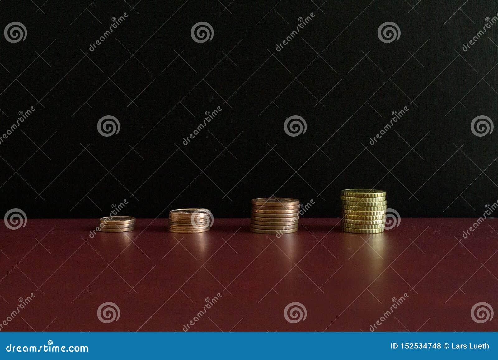 4 piccole pile di euro monete dei soldi in una fila