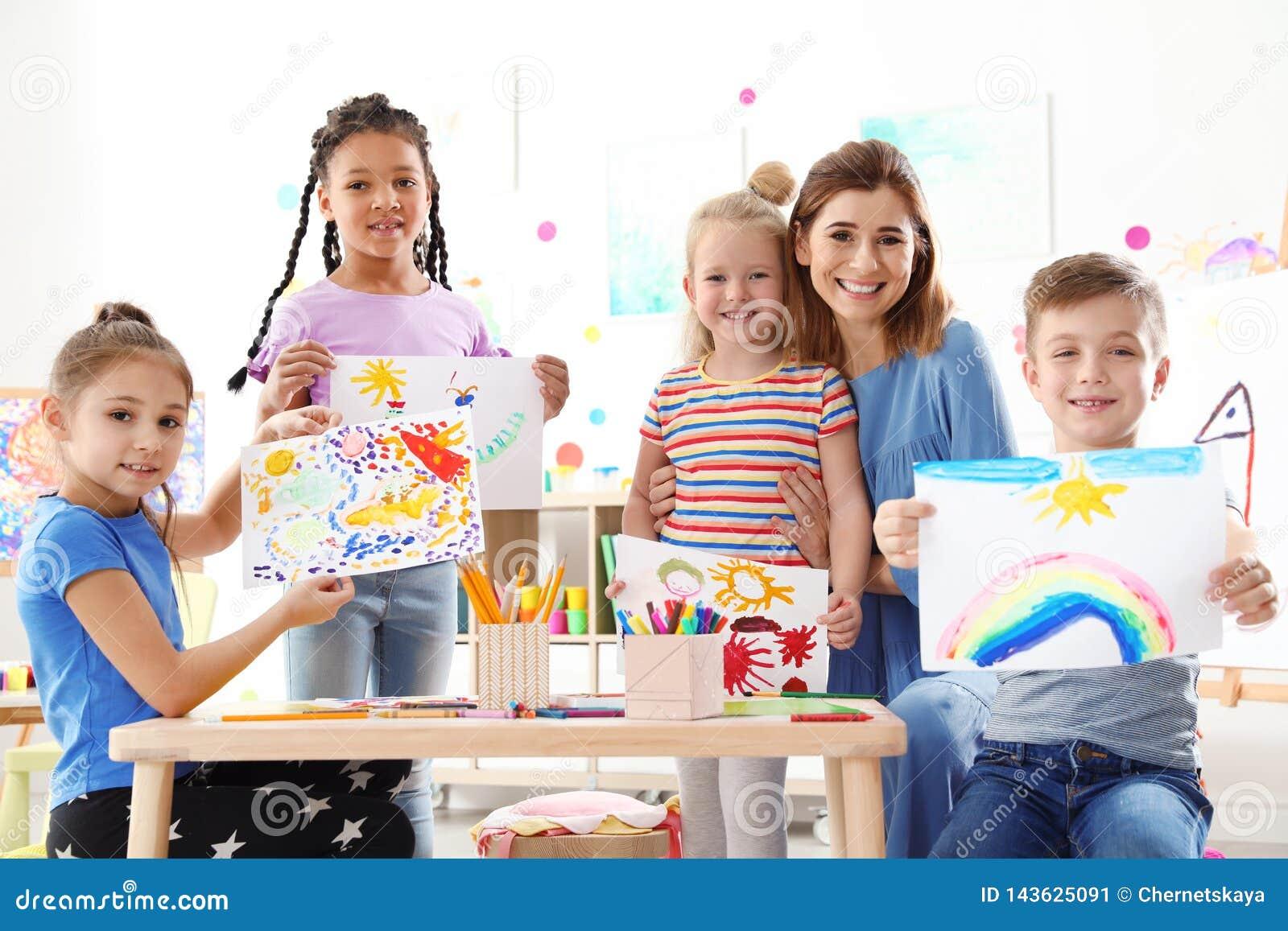Piccoli bambini svegli con l insegnante che mostra le loro pitture alla lezione