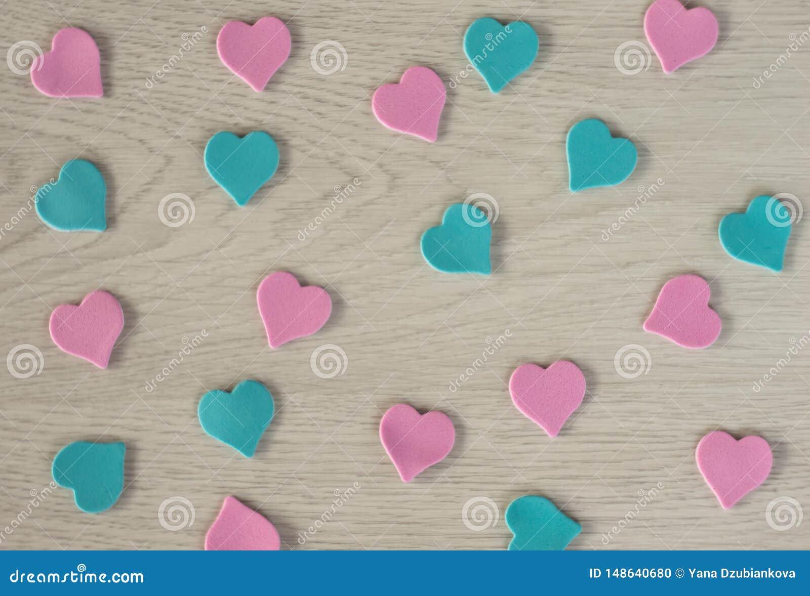 Piccoli cuori del rosa e della bugia blu di colore su una tavola di legno bianca
