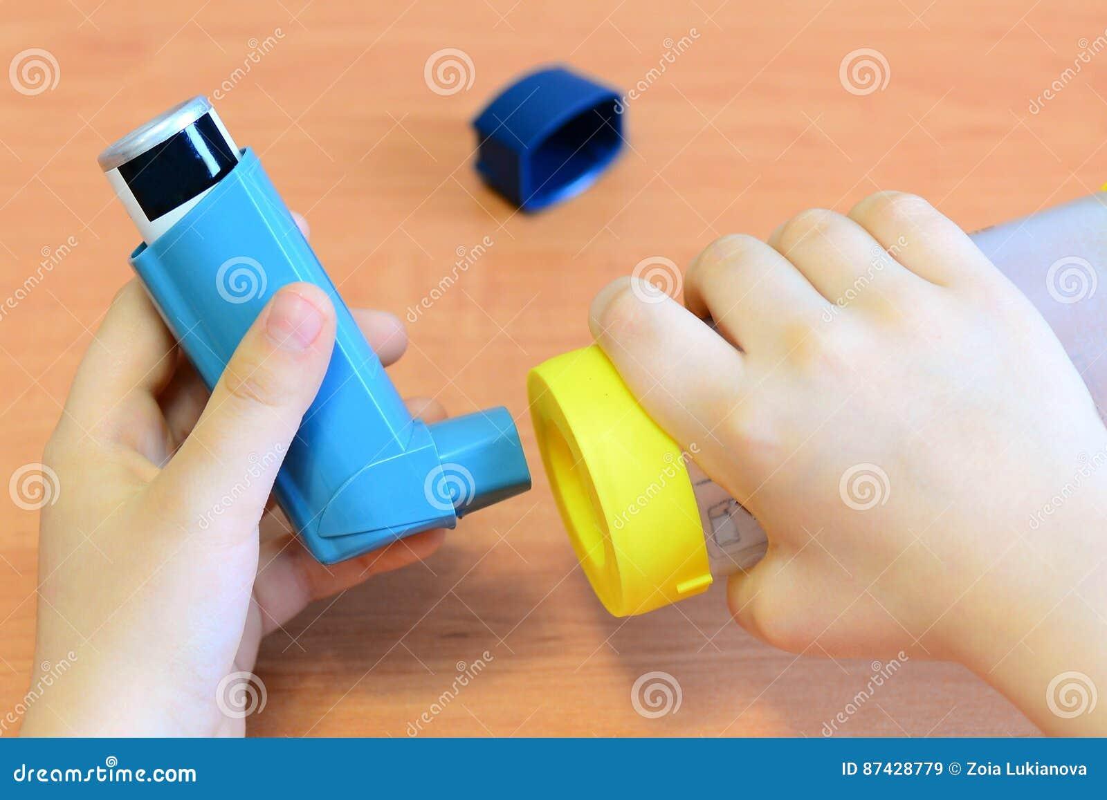Piccoli inalatore e distanziatore di asma della tenuta del bambino in sue mani Distanziatore di asma ed inalatore dell aerosol