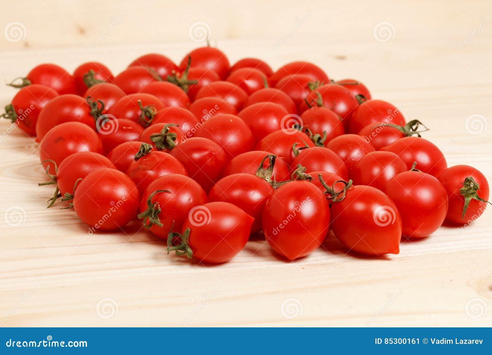 Piccoli pomodori ed erbe fresche su fondo di legno