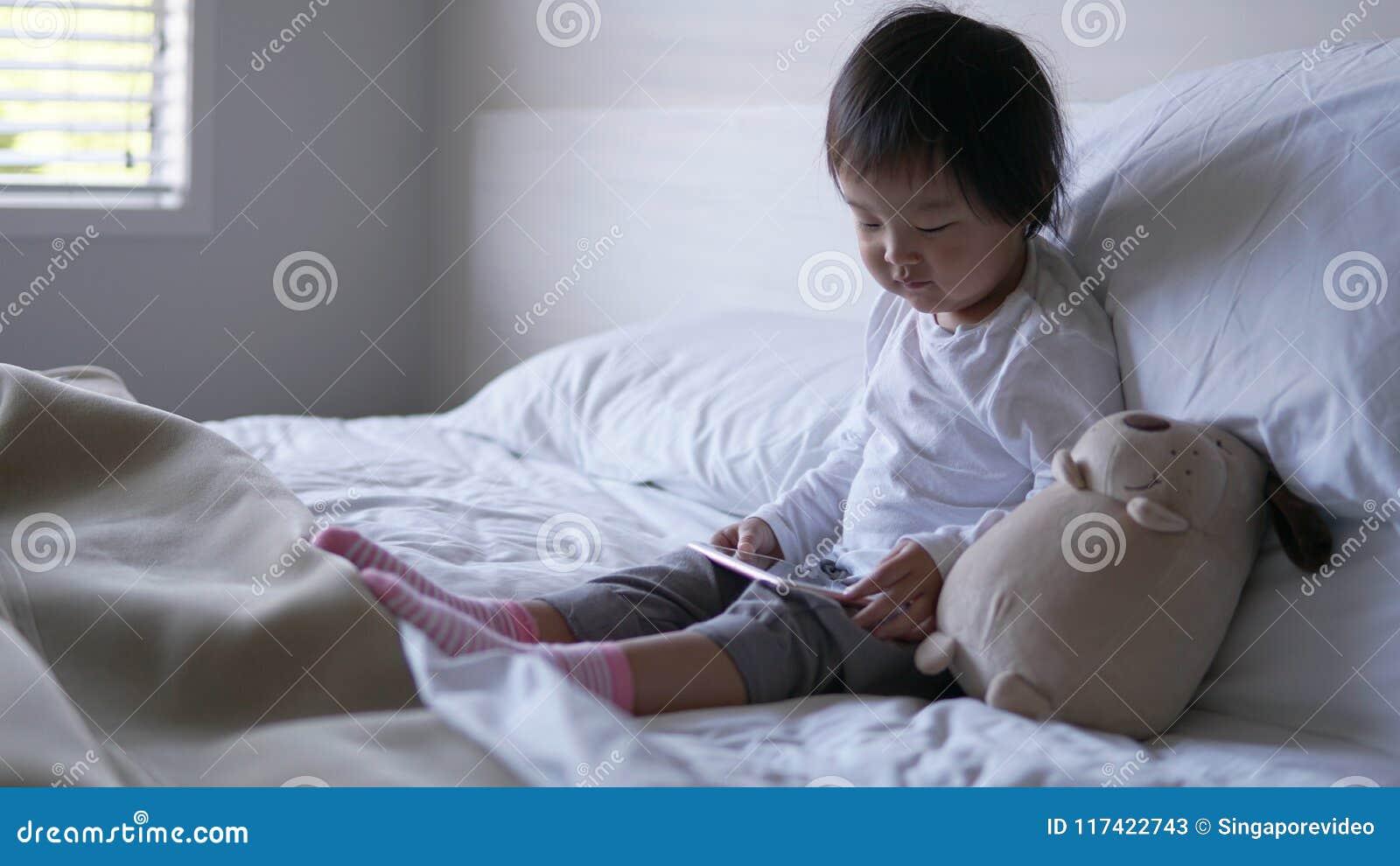 Le Cinesi A Letto.Piccolo Bambino Cinese Asiatico Che Si Siede Sul Letto Dipendente