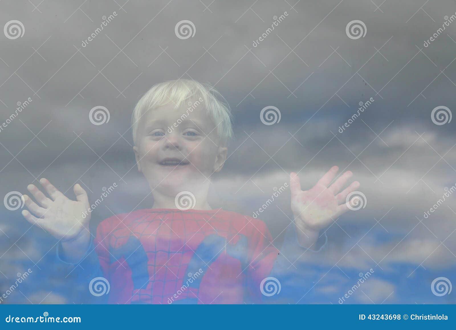 Piccolo bambino felice che guarda fuori la finestra