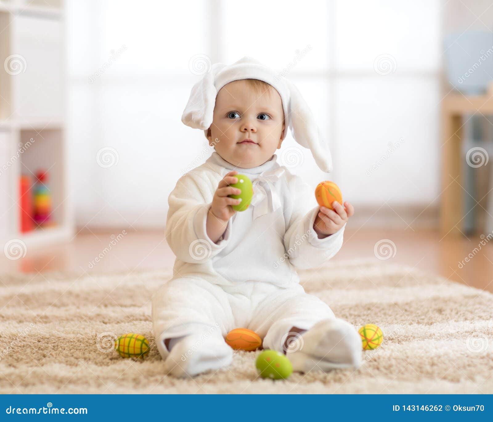 Piccolo bambino sveglio in costume bianco del coniglietto che si siede sulla coperta a casa