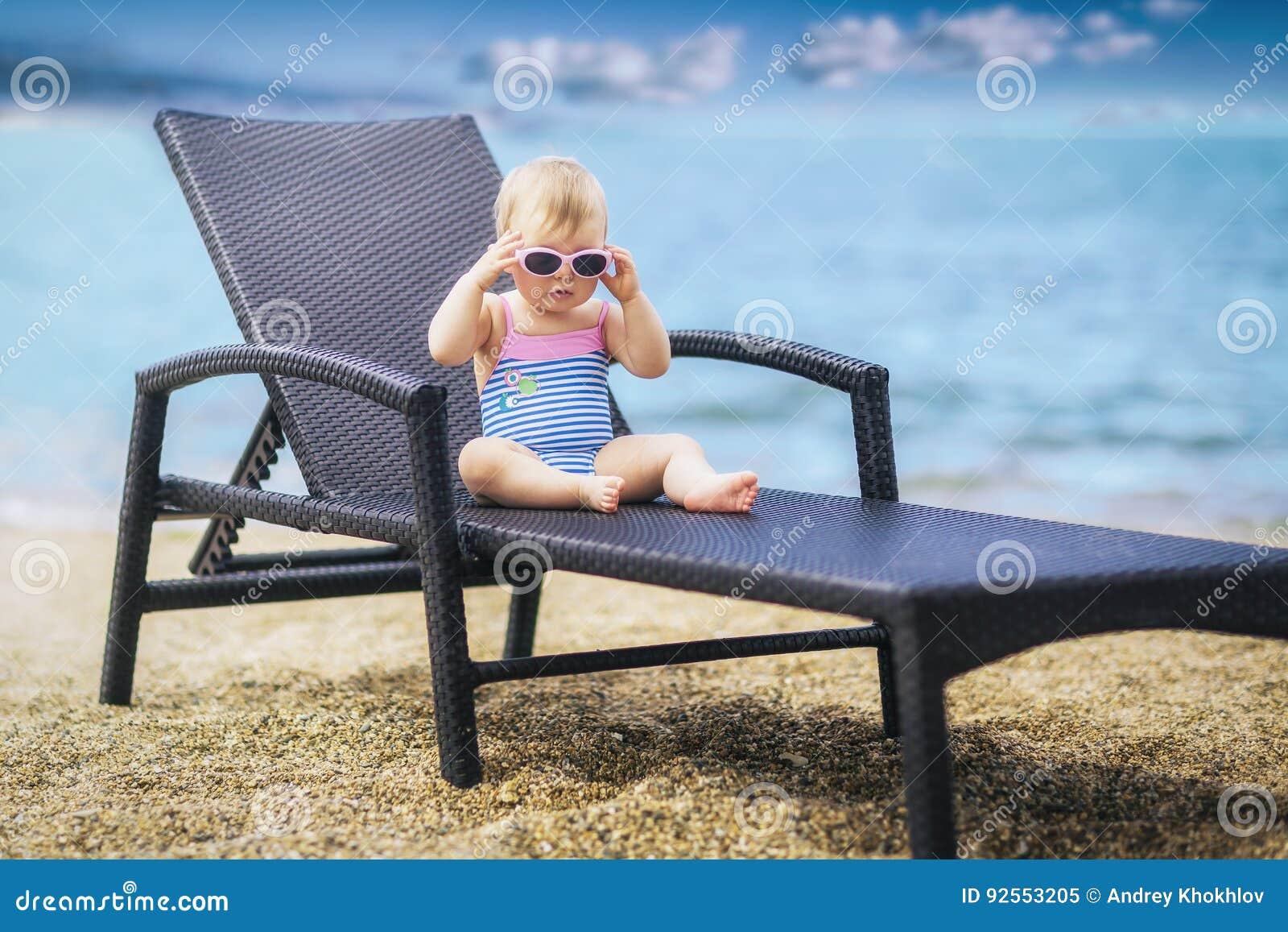 Piccolo bambino sveglio in costume da bagno ed occhiali da sole rosa d uso