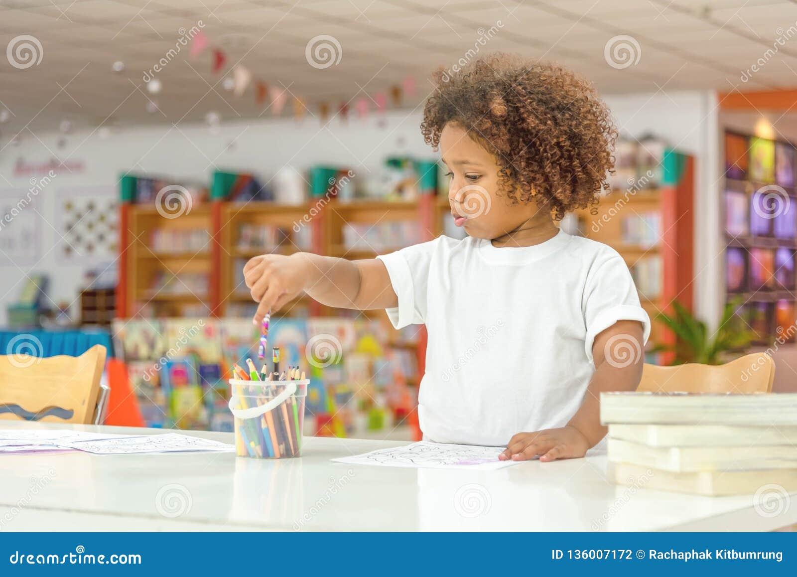 Piccolo concentrato della ragazza del bambino sul disegno Ragazza africana della miscela imparare e giocare nella classe della sc