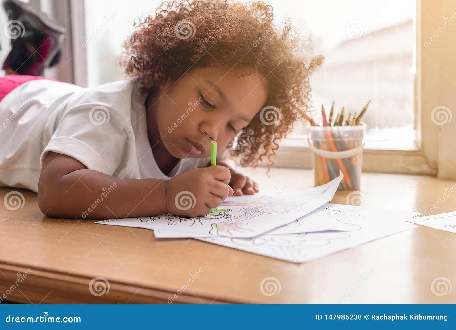 Piccolo concentrato di indicazione della ragazza del bambino sul disegno Ragazza africana della miscela imparare e giocare nella