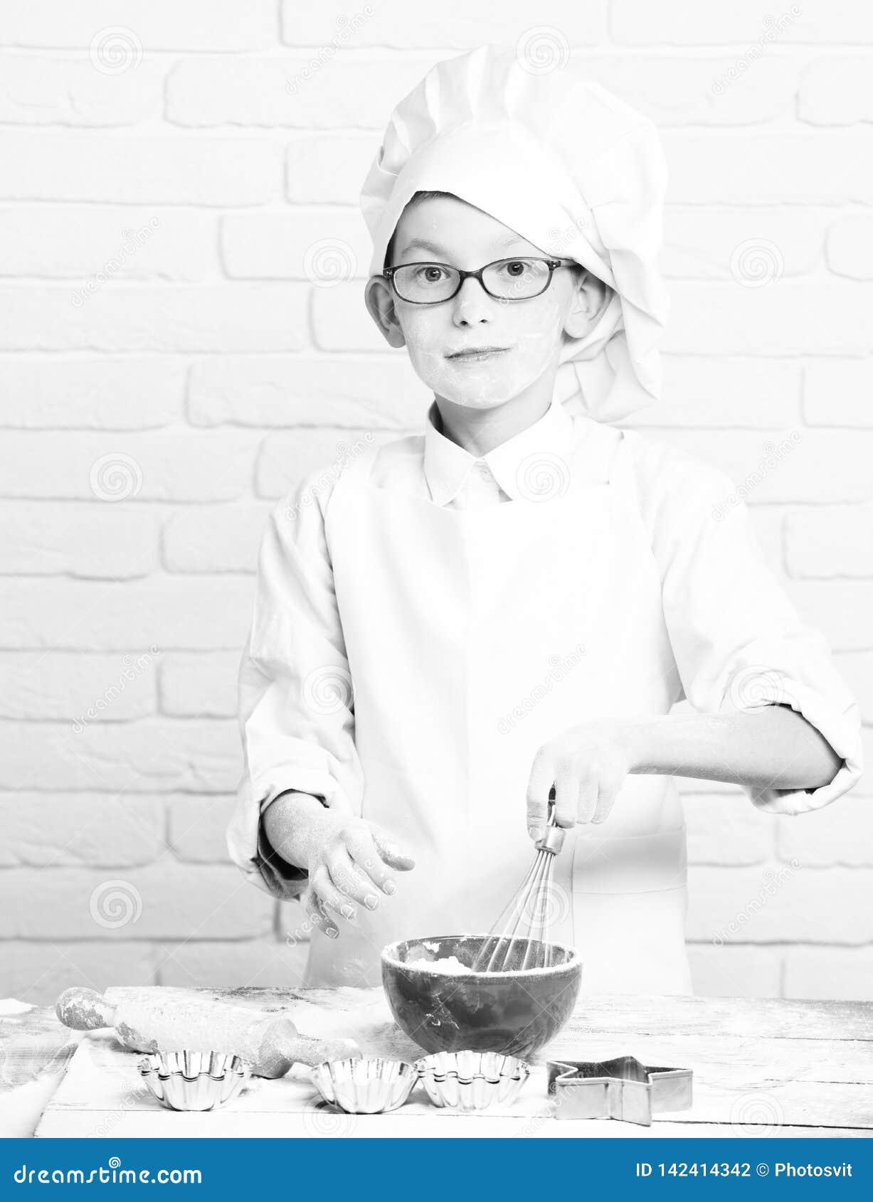 Piccolo cuoco unico sveglio del cuoco del giovane ragazzo in uniforme e cappello di bianco sul fronte felice con i vetri che stan