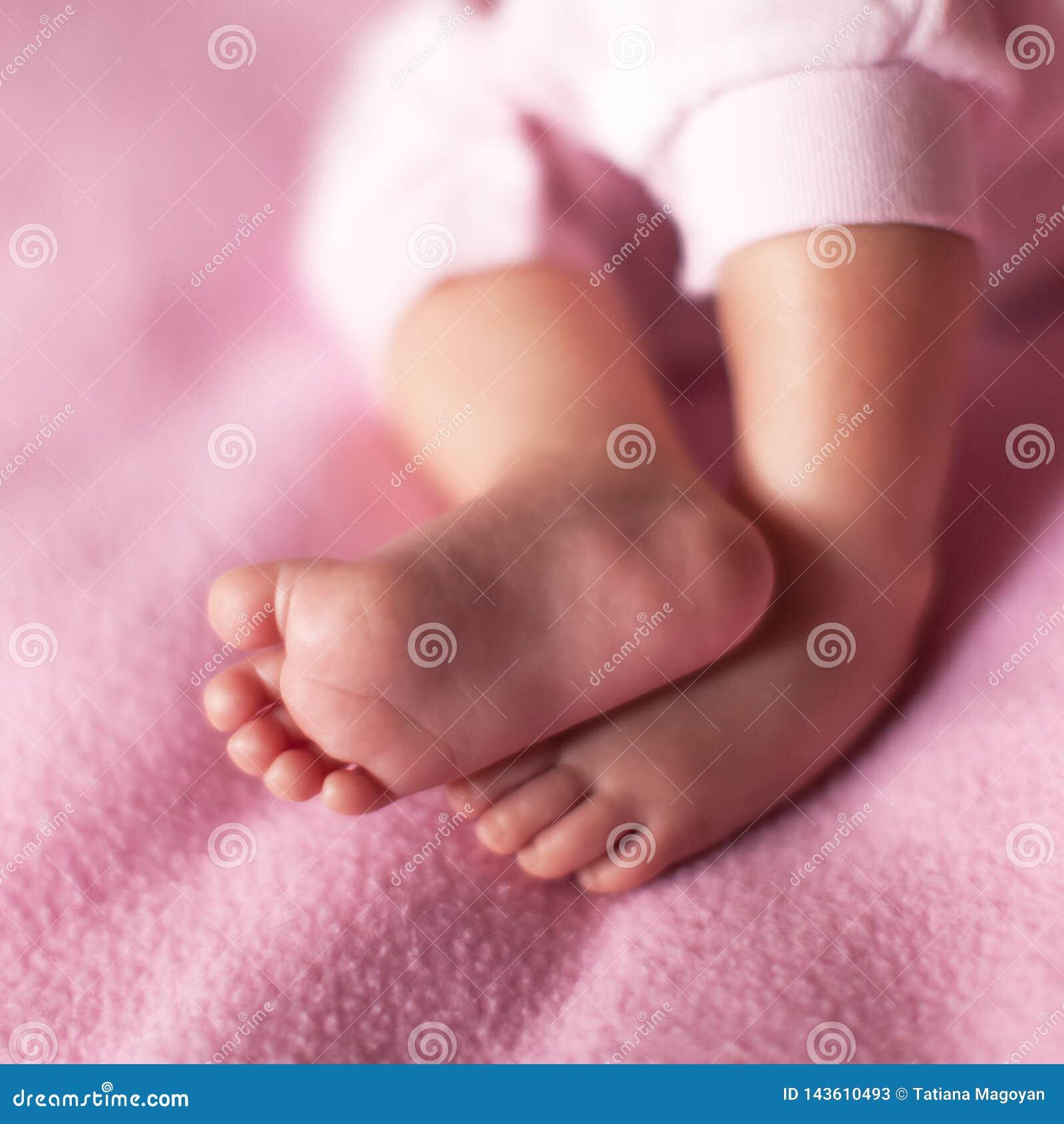 Piccolo gambe dolci della neonata su fondo rosa Concetto: bambini, paternit?, famiglia, doccia di bambino Formato quadrato per i