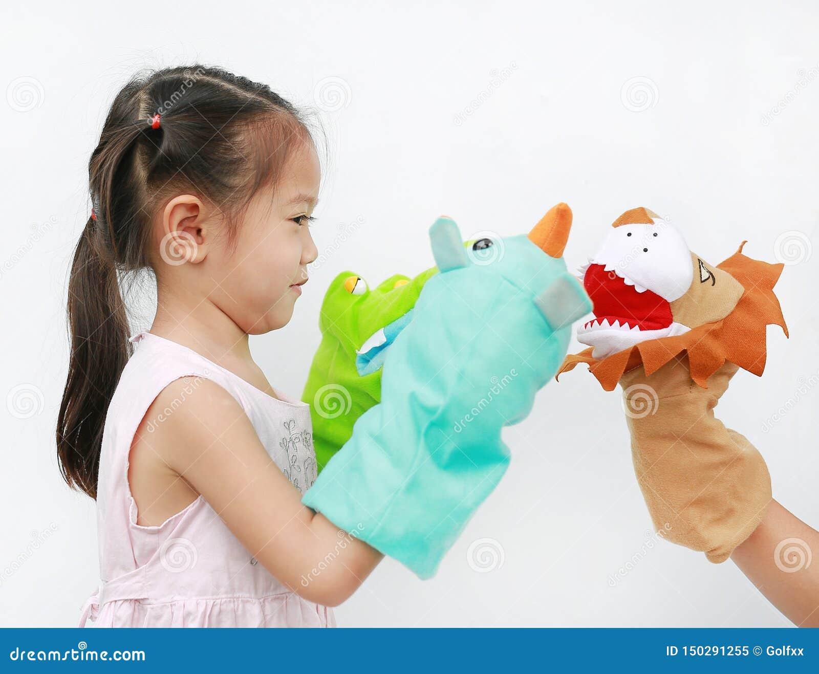 Piccolo mani asiatiche della ragazza del bambino che giocano i burattini animali con la mano di sua madre su fondo bianco Concett