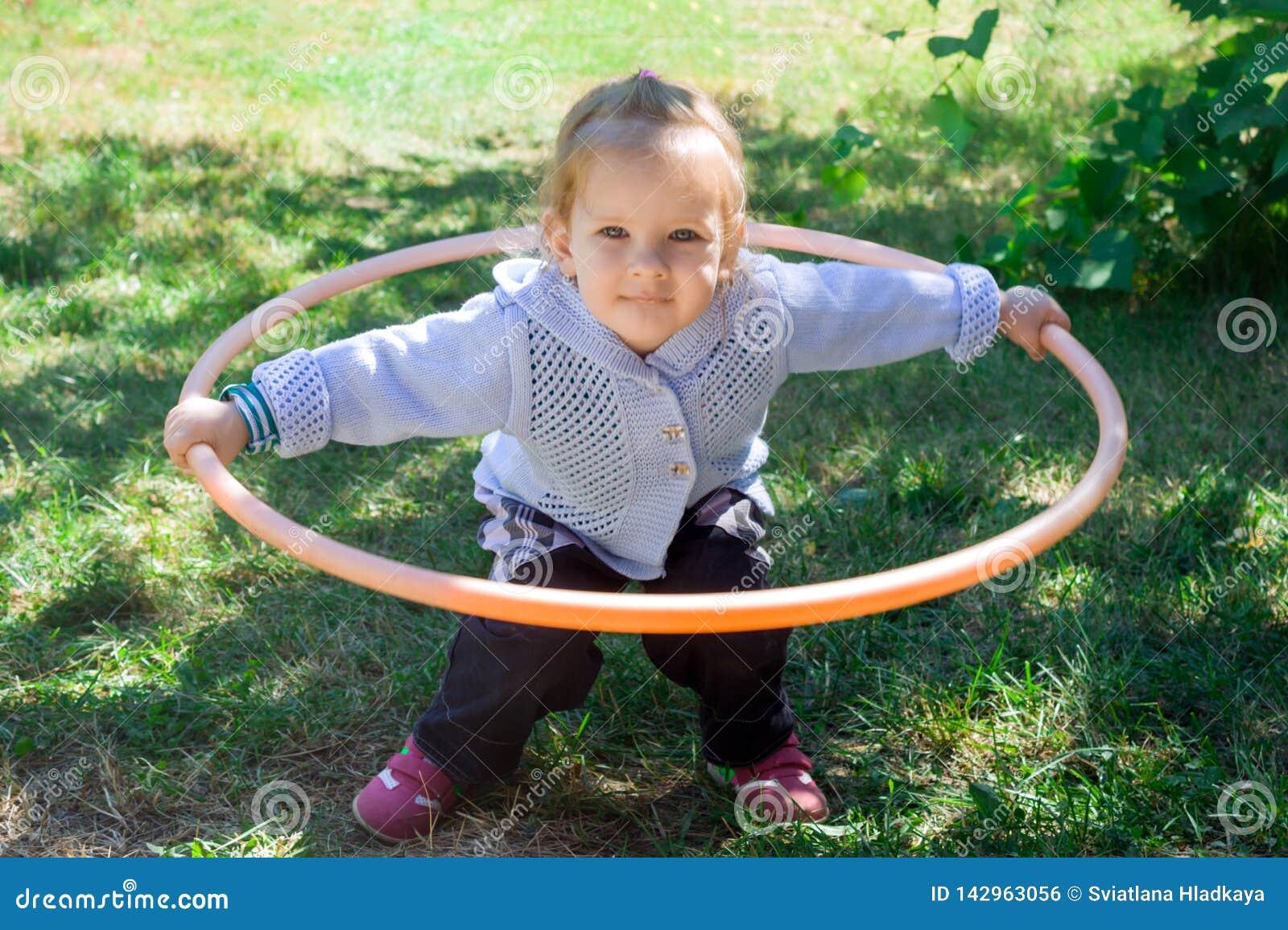 Piccolo neonata impara occuparsi di hulahup Il bambino tiene il cerchio con due mani