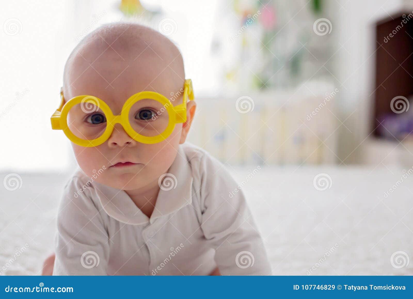 Piccolo neonato, bambino, giocante a casa con i vetri divertenti dell occhio