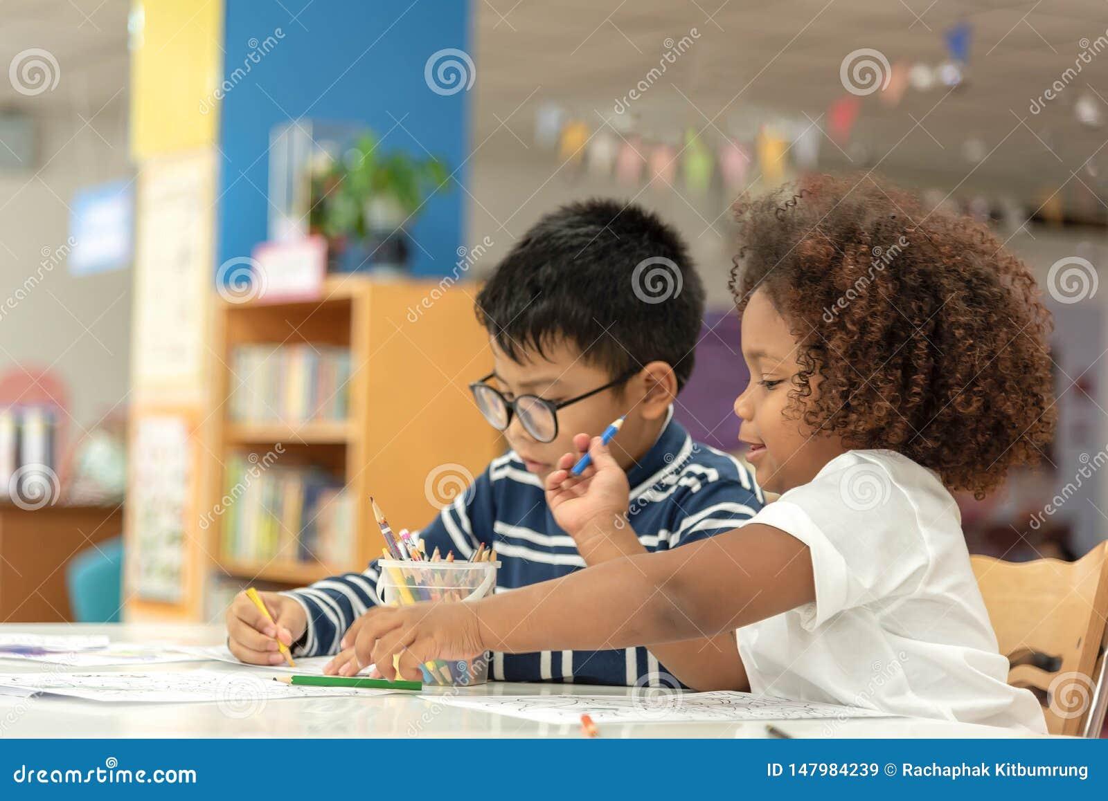 Piccolo ragazza e ragazzo del bambino che riuniscono Ragazzo asiatico e mescolare ragazza africana per imparare insieme e giocare