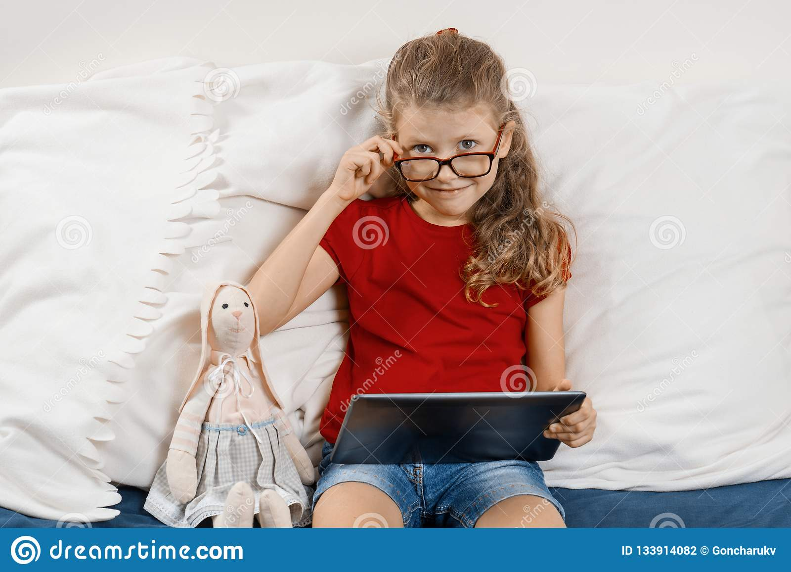 Piccolo ragazza graziosa in vetri che si siedono a casa a letto con il giocattolo e compressa digitale, resto e istruzione a casa