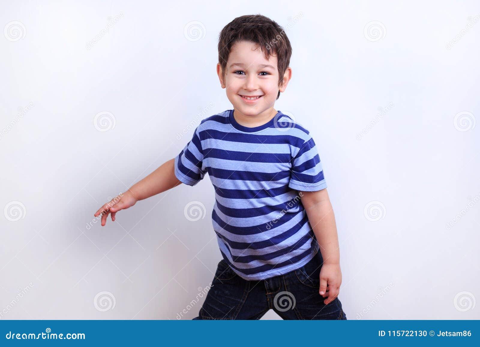 Piccolo ragazzo adorabile che sorride e che posa, tiro dello studio su bianco Emo