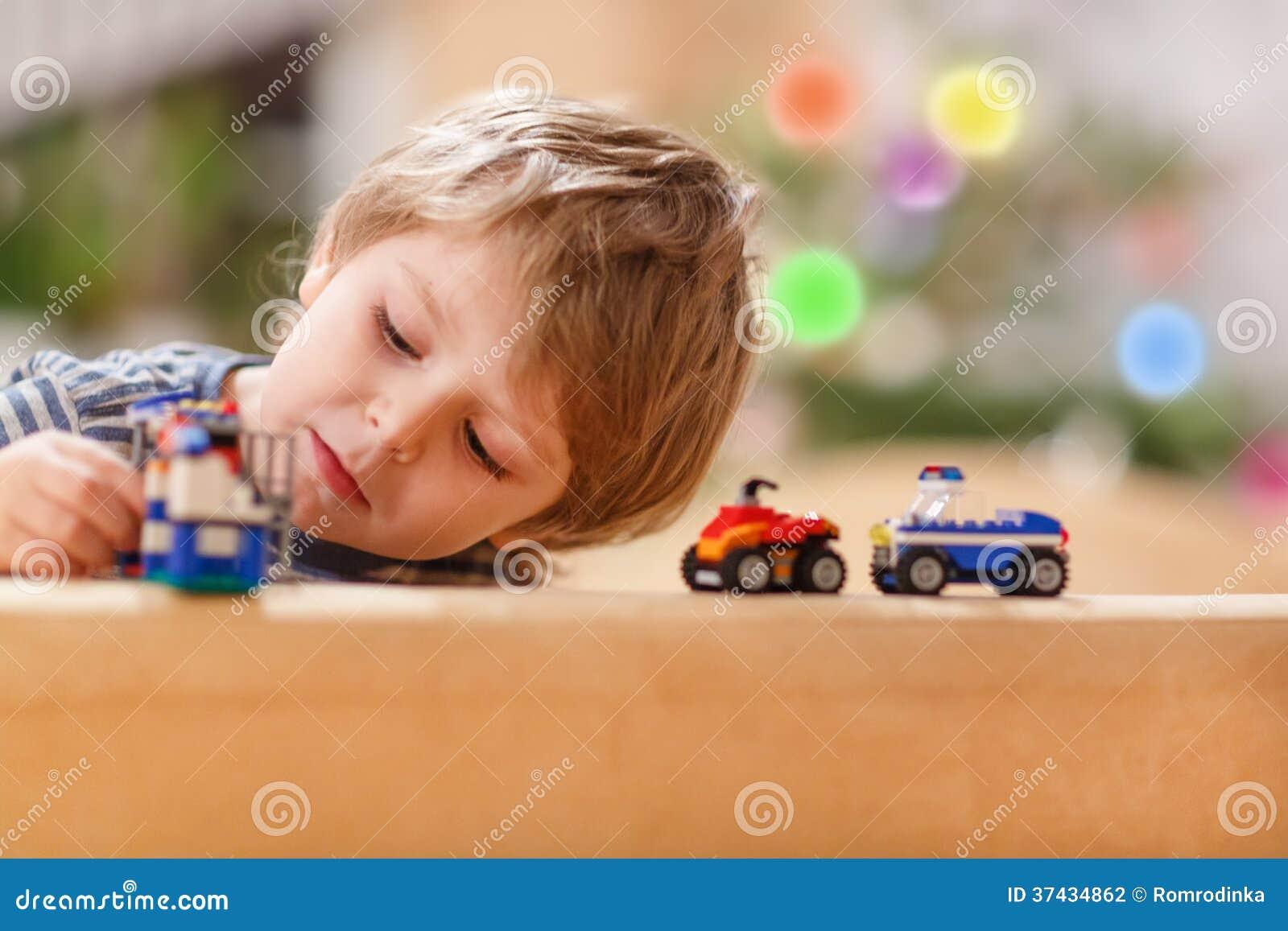 Piccolo ragazzo biondo che gioca con le automobili ed i giocattoli a casa, dell interno.