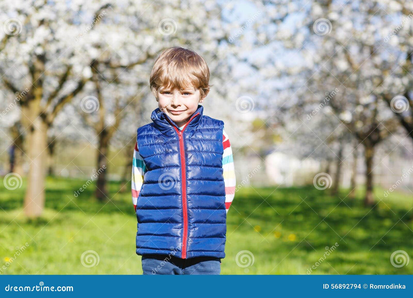 Piccolo ragazzo biondo del bambino divertendosi sul giardino di fioritura della ciliegia