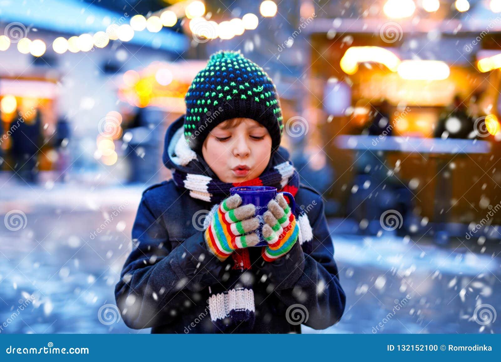 Piccolo ragazzo sveglio del bambino che beve la perforazione o il cioccolato calda dei bambini sul mercato tedesco di Natale Bamb