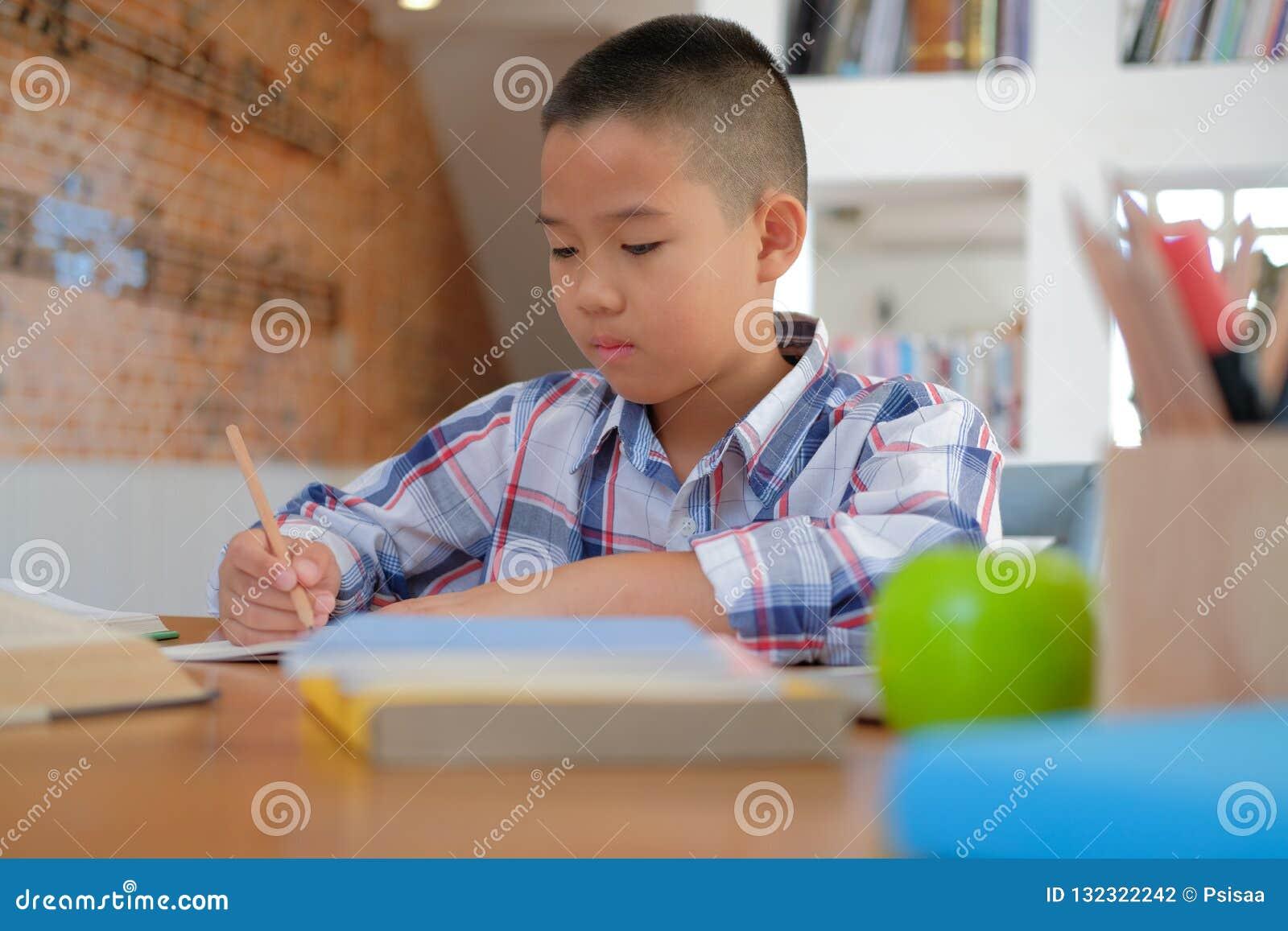 Piccolo scolaro asiatico del ragazzo del bambino che scrive attingendo taccuino Chil