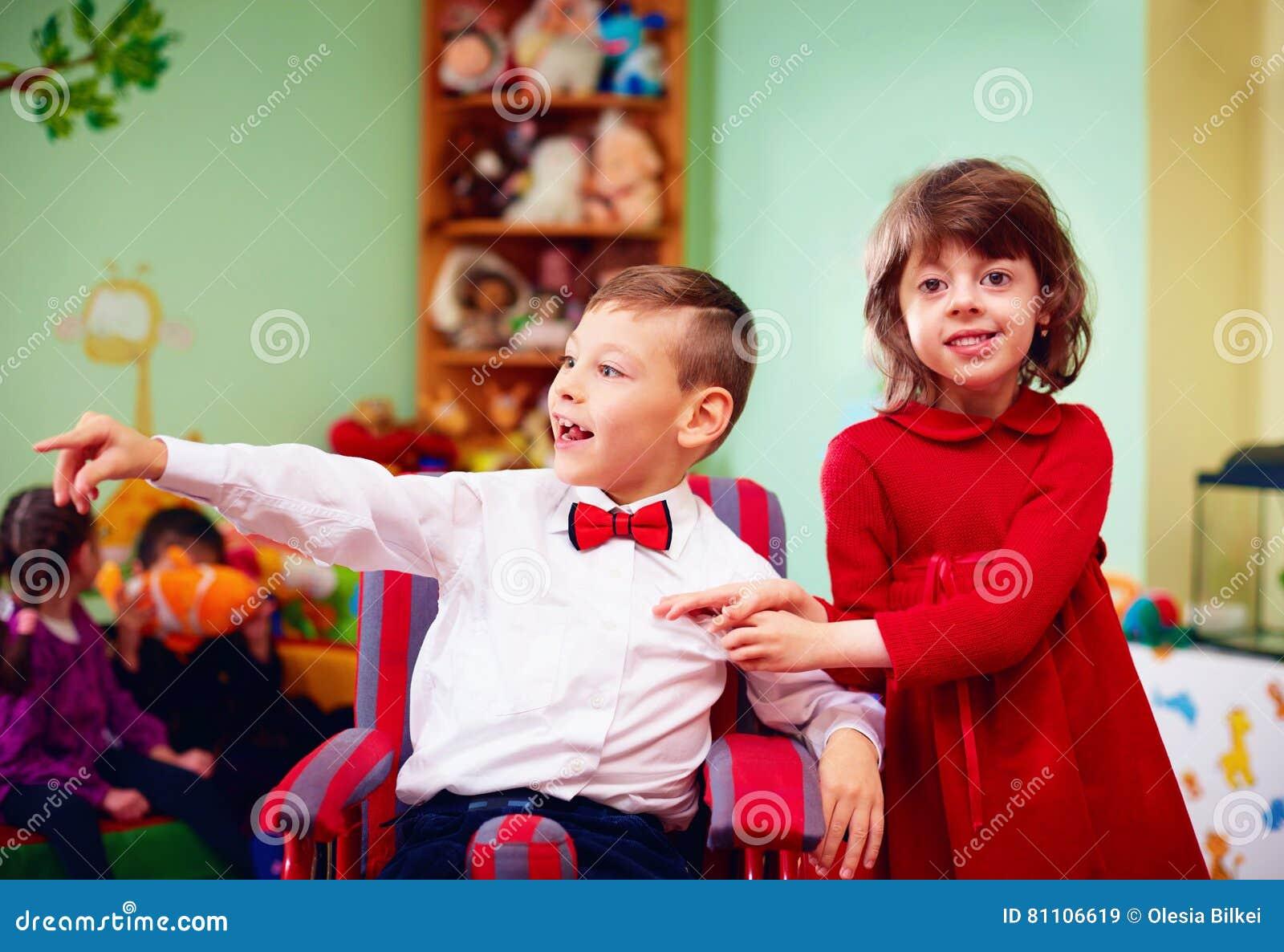 Piccolo signore sveglio in sedia a rotelle ed in signora for Fisico sedia a rotelle
