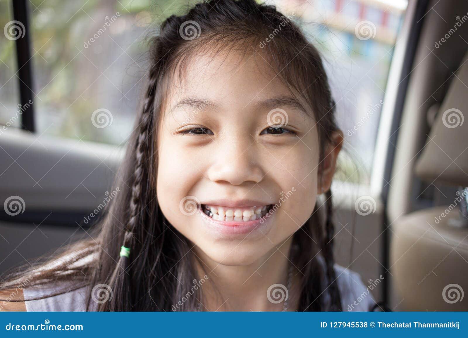 Piccolo sorriso sveglio della ragazza con il suo dente rotto