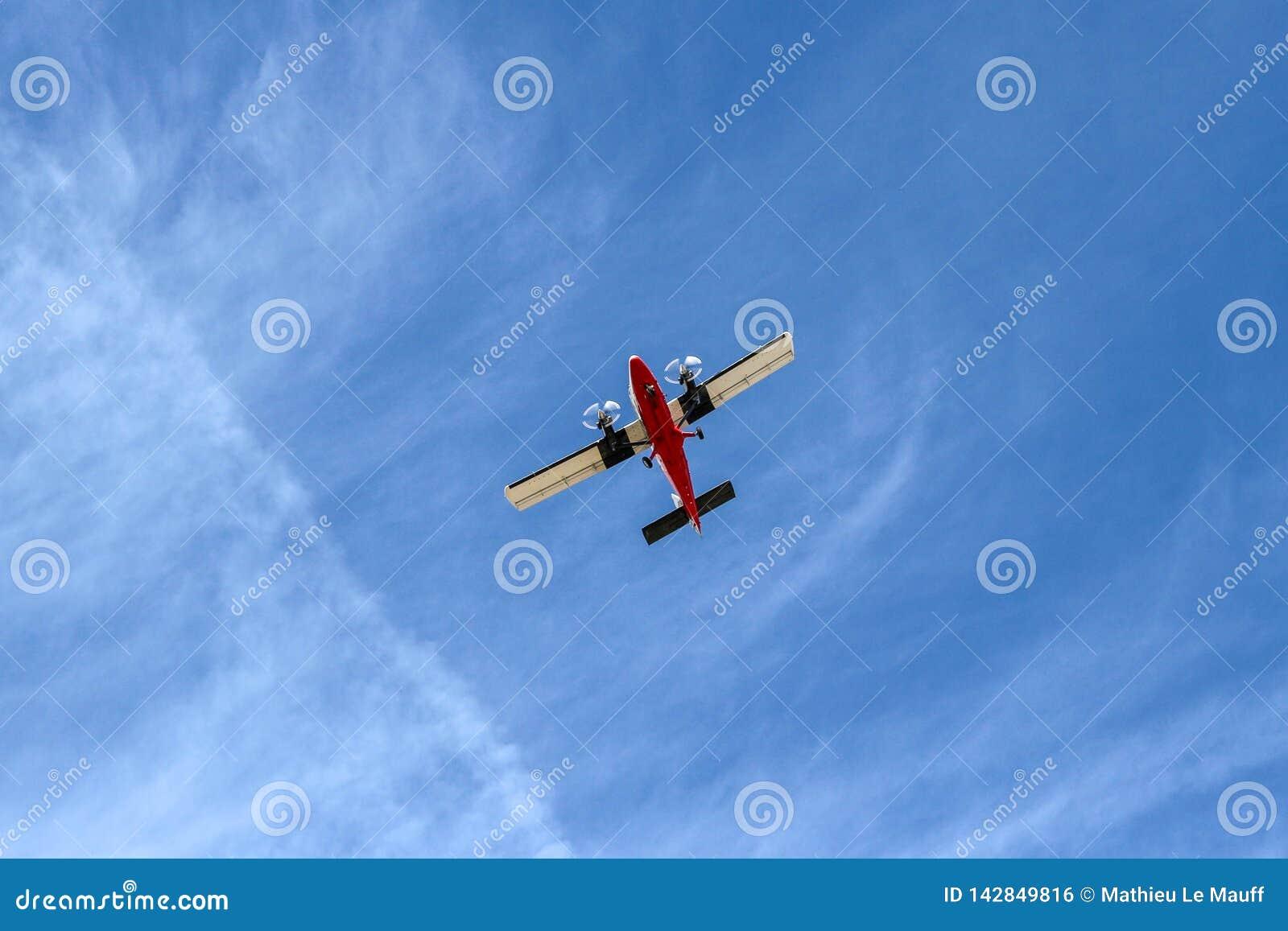 Piccolo volo dell aeroplano alla bassa quota sotto cielo blu osservato da sotto