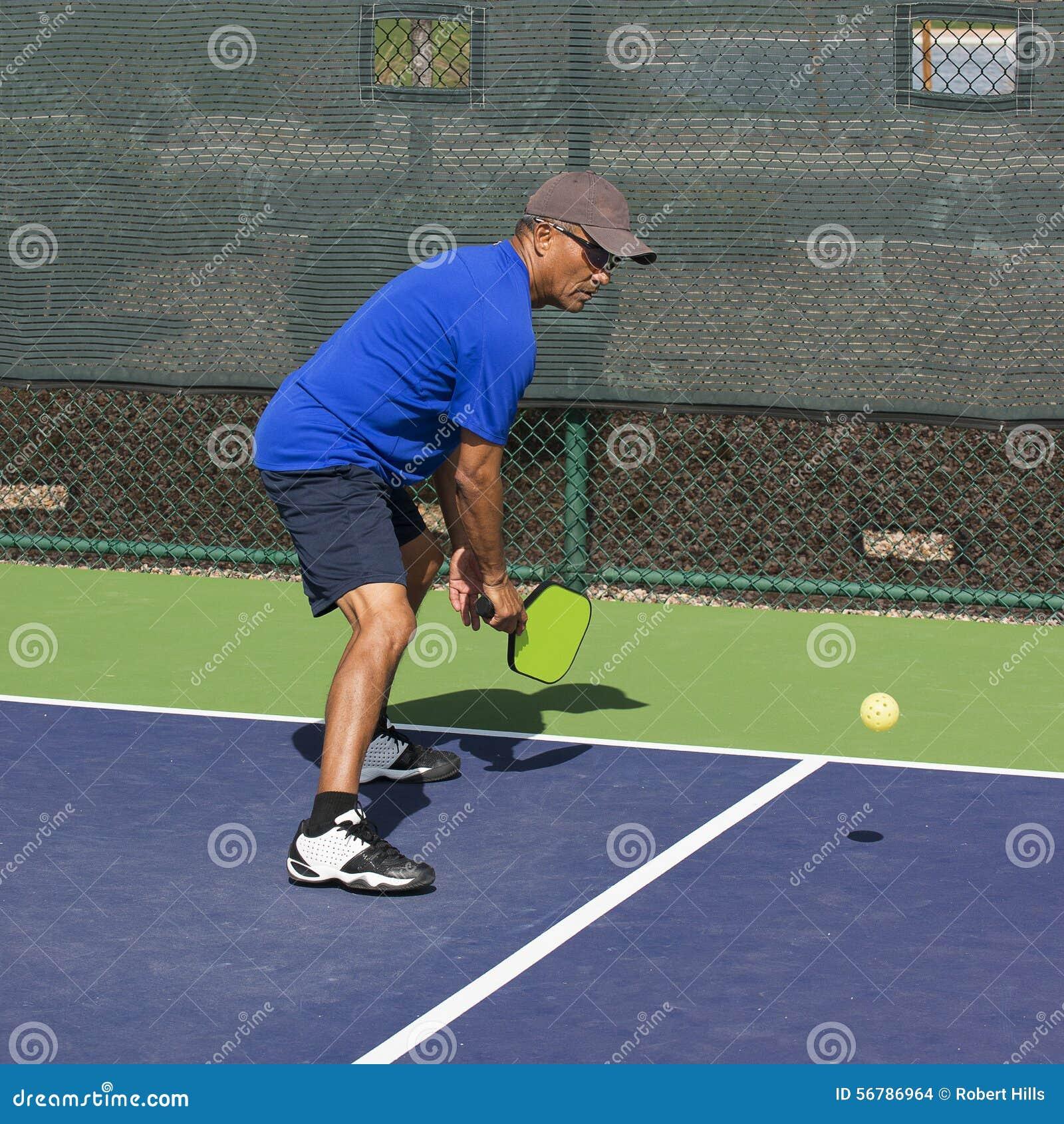 Pickleball akcja - mężczyzna w Błękitnym narządzaniu Uderzać backhanda Dink