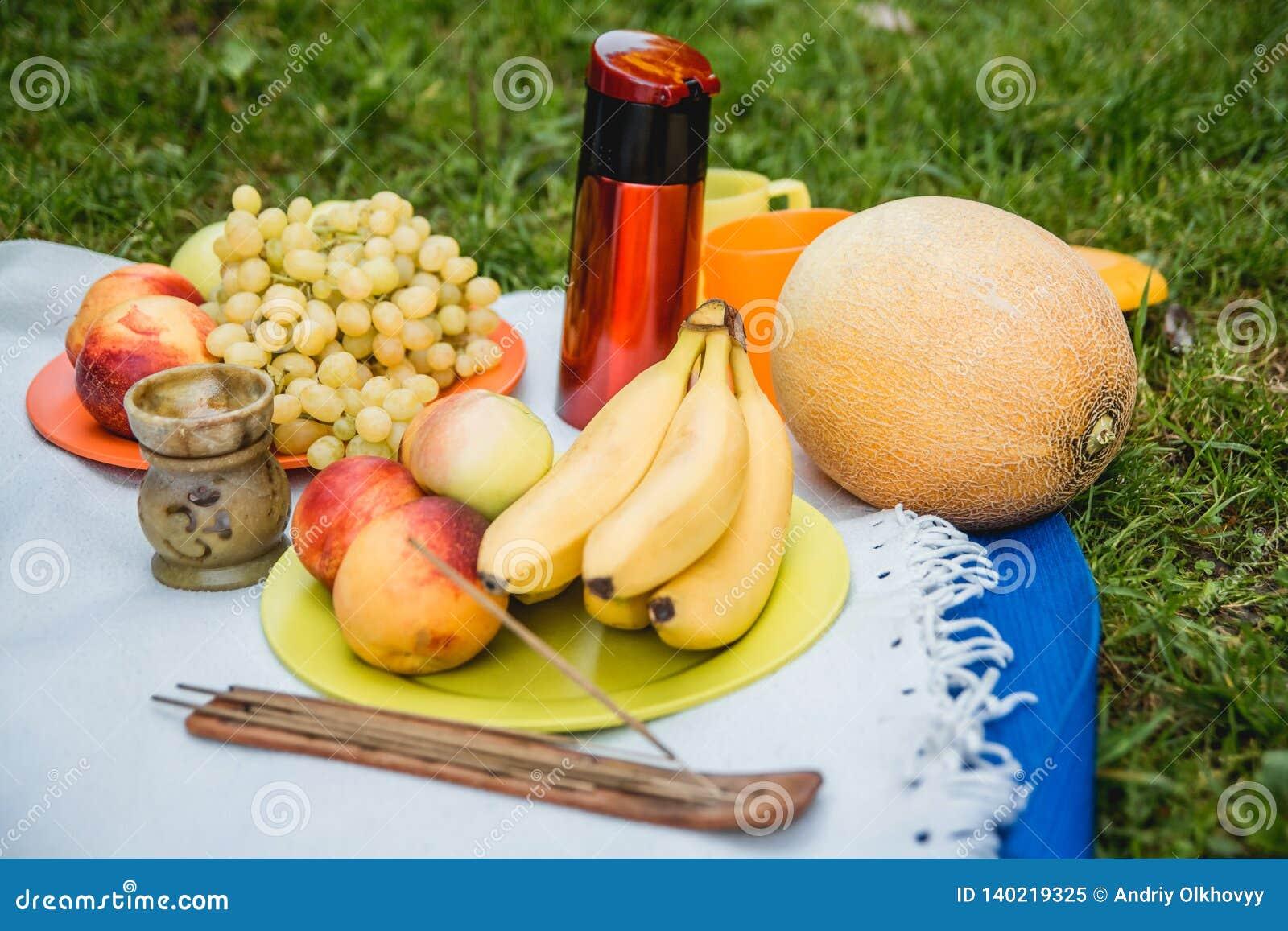 Picknickbakgrund med vitt vin och sommar bär frukt på grönt gräs