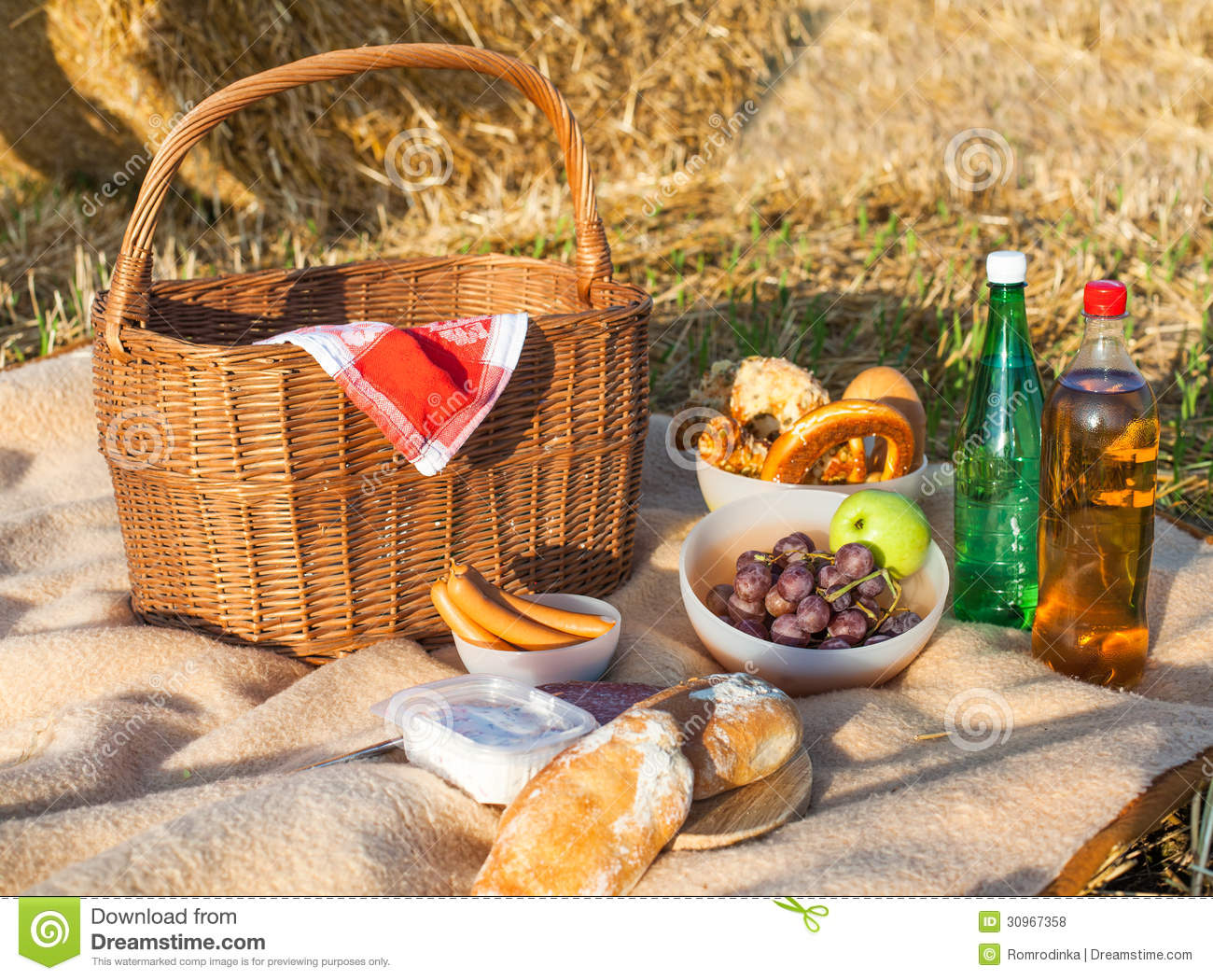 Picnic Basket Food : Picnic basket and different food drinks on straw field