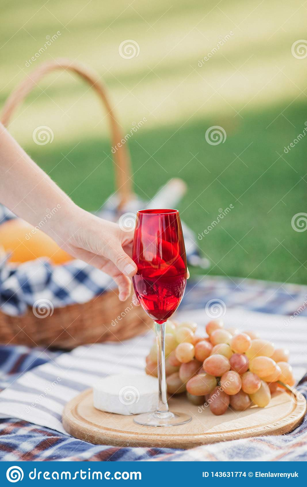 Picnic basket with drinks, food and fruit on green grass outside in summer park
