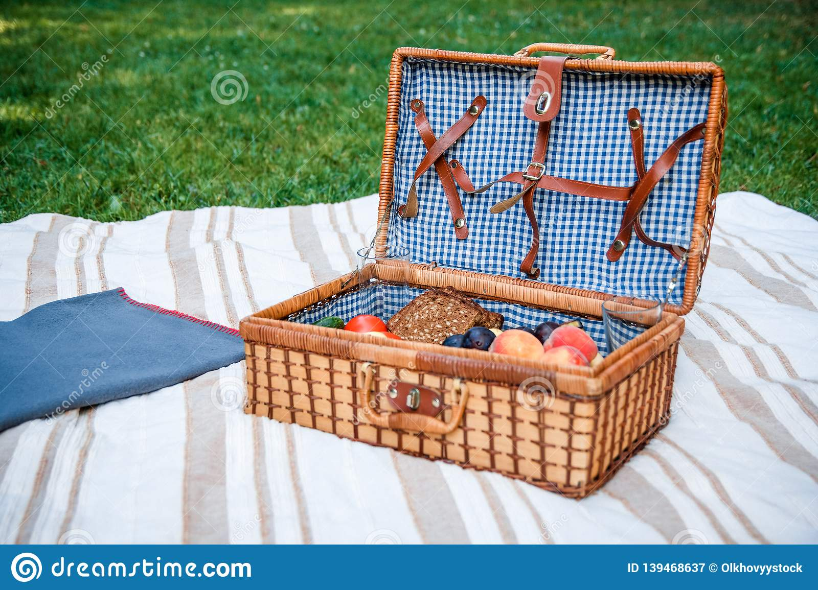 Picnic basket with fruits on the grass background