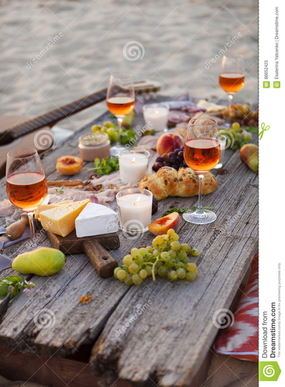 Picnic on the beach at sunset in boho style, food and drink conc