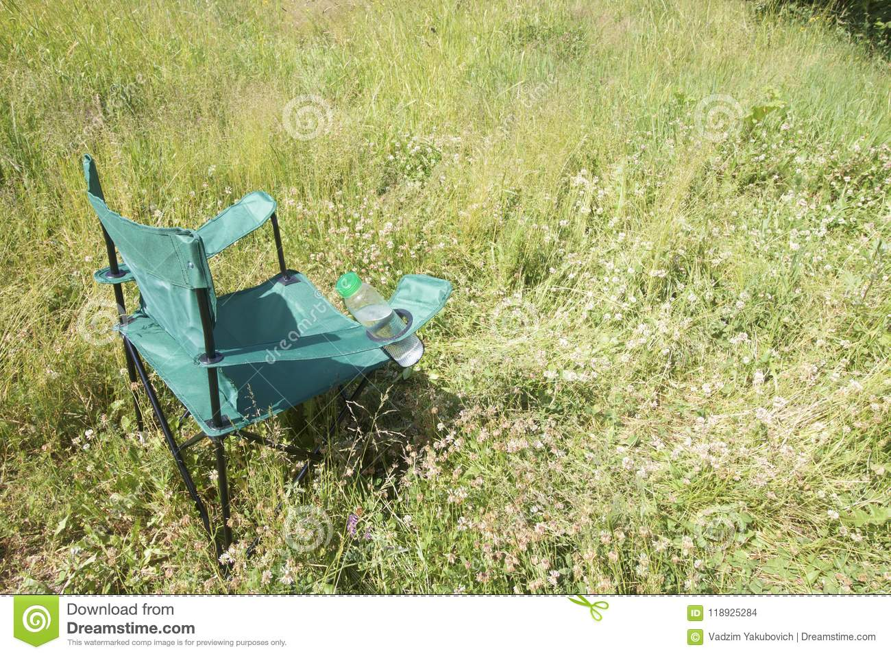 A Picnic Chair Stands On A Light Flooded Meadow. In The Stand Is A