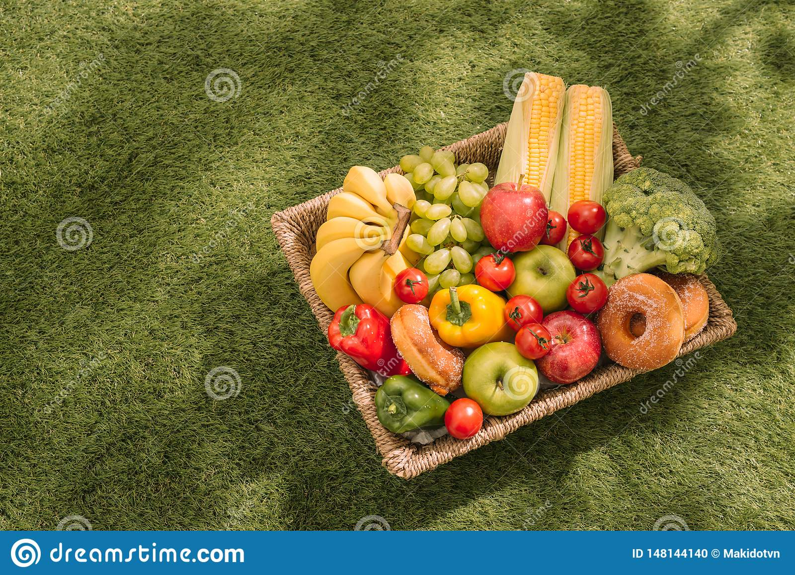 Picnic on the grass. Red checked tablecloth, basket, healthy food and fruit, orange juice. Top view. Summer Time Rest. Flat lay