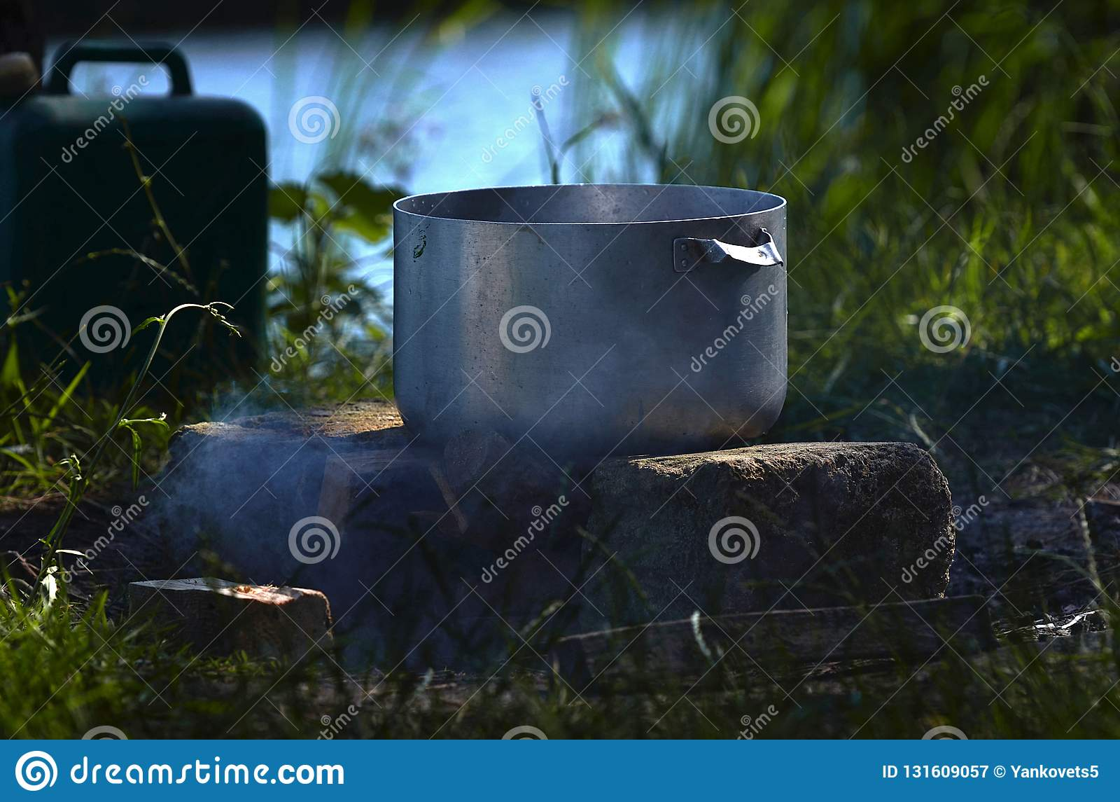 At a picnic near the river, a large metal pan in which fish soup is prepared against the background of green grass and smoke