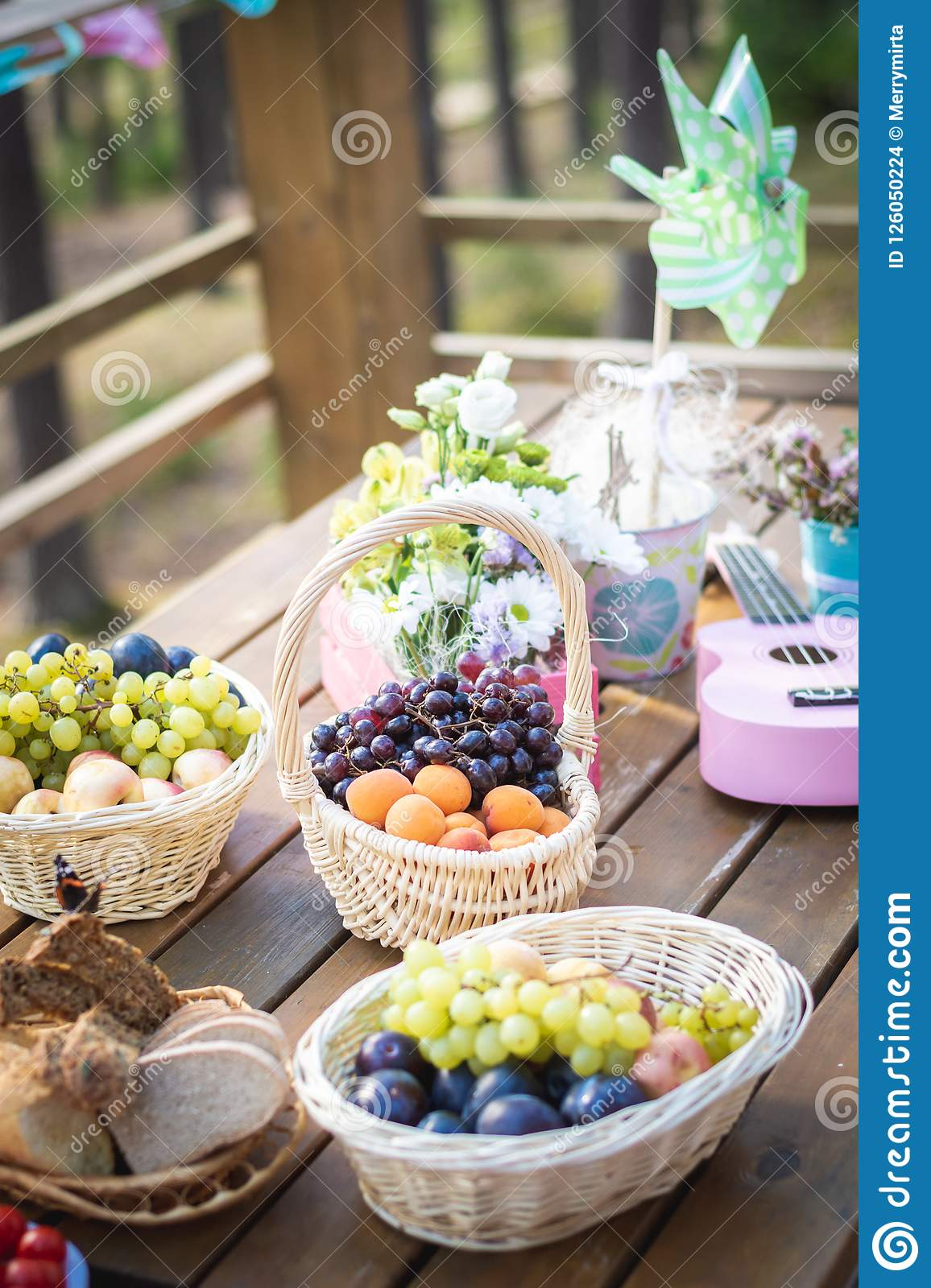Picnic Party Table Decoration Baskets With Fruits On A Wooden Table Flowers Pink Small Guitar And Pinwheel Stock Photo Image Of Food Celebration 126050224